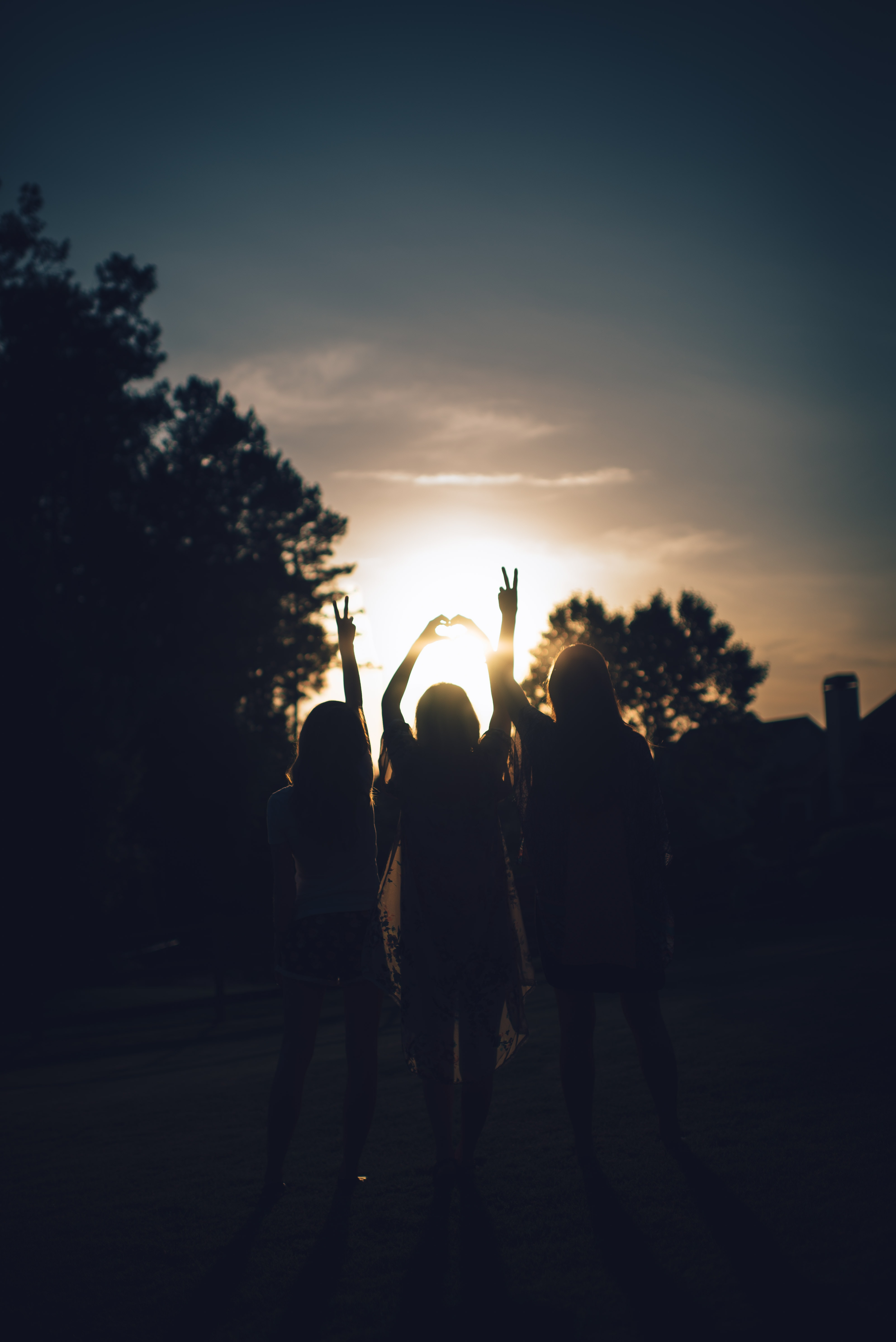 Silhouette of three girls holding up peace signs and a heart hand sign during sunset