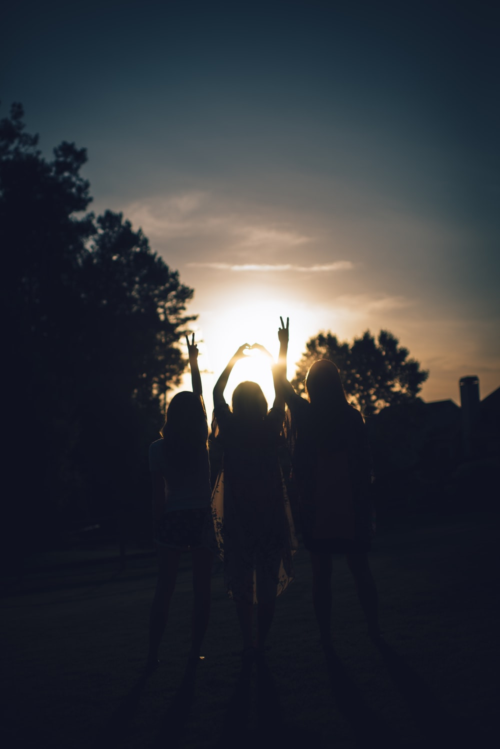 silhouette of three women during daytime