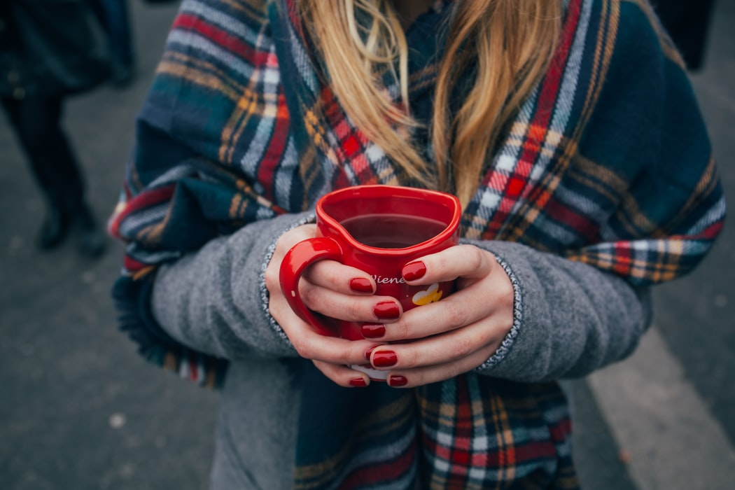 woman with flannel scarf holding a cup of coffee