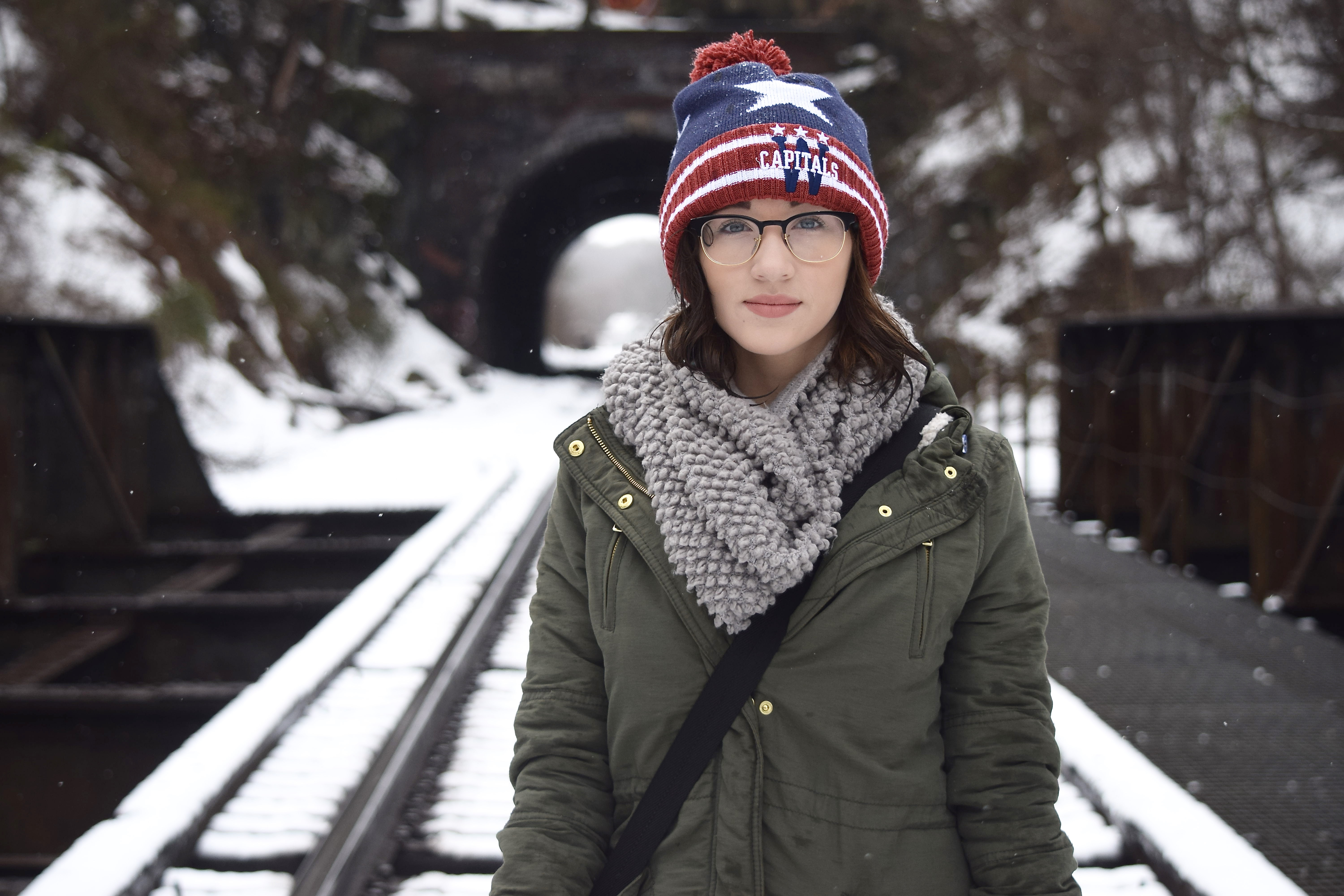 A girl with is walking on a snowy train track in front of a tunnel