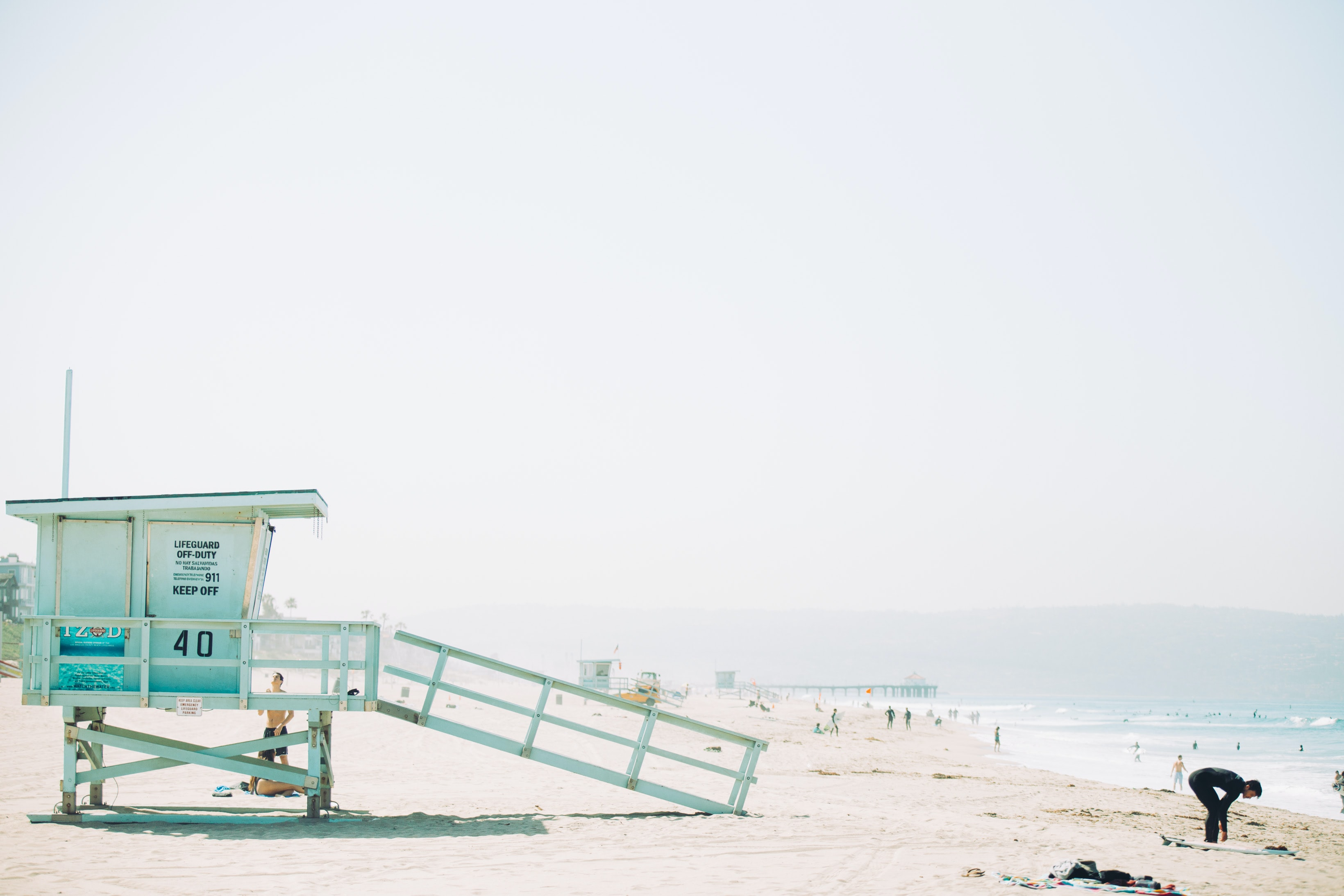 man standing in front of green wooden life guard station in seashore during day time