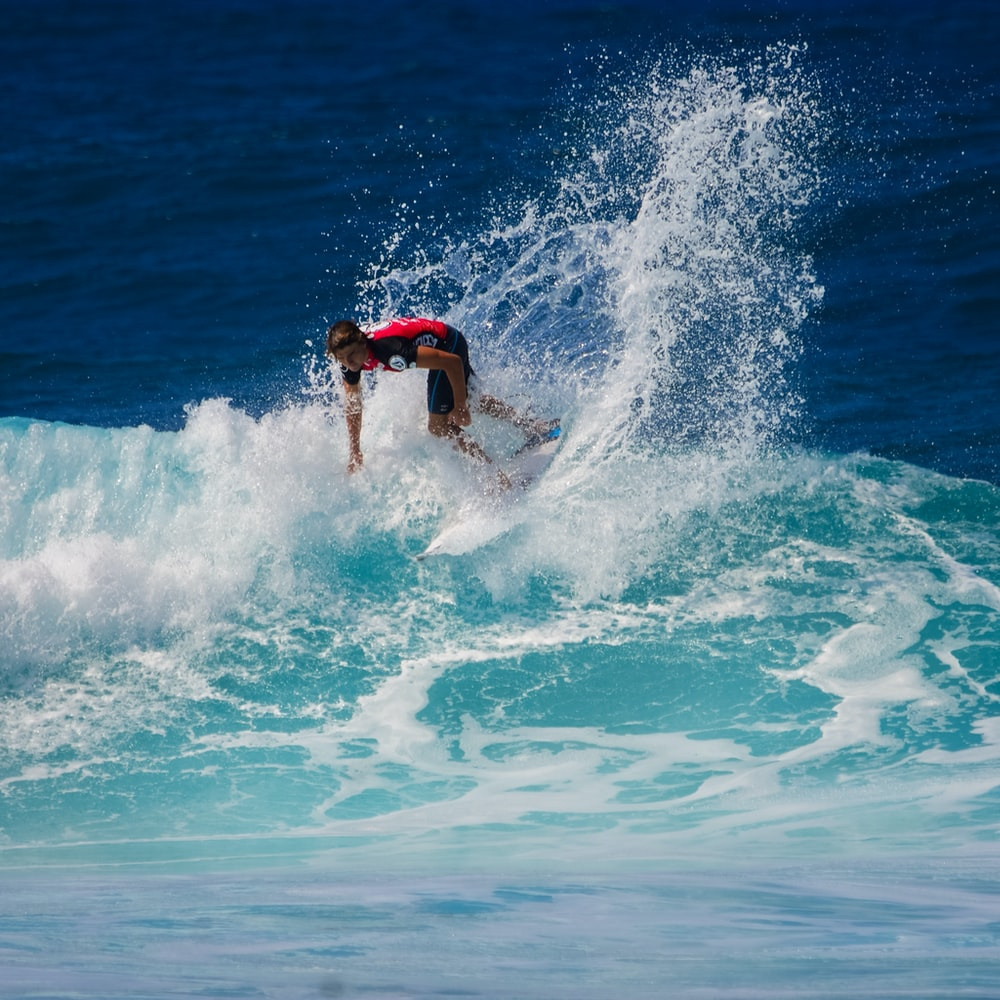 man using surfboard in wave of body of water during daytime