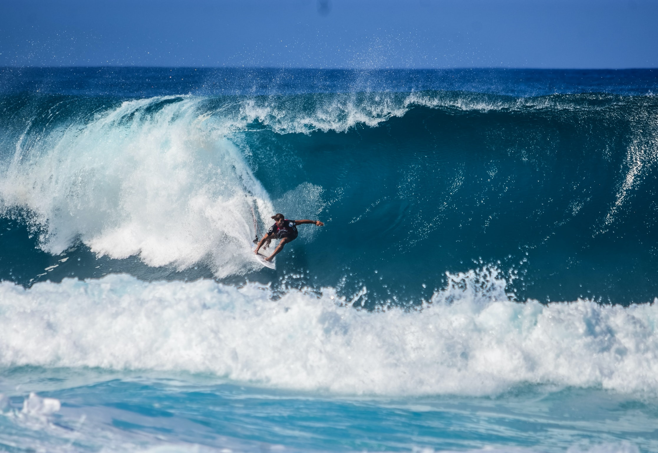 A surfer riding a large wave in the blue sea, underneath a blue sky