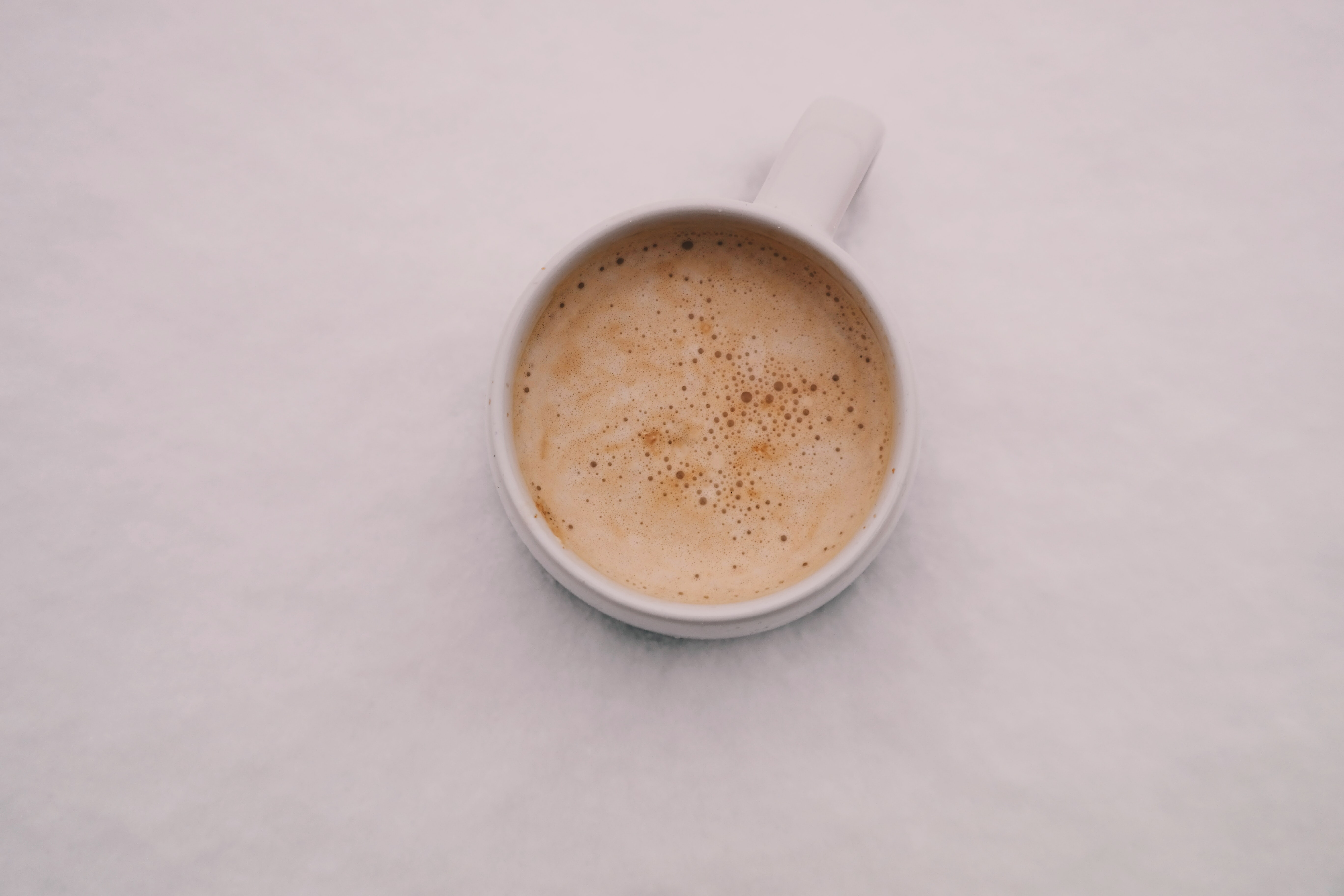 white cup with beverage