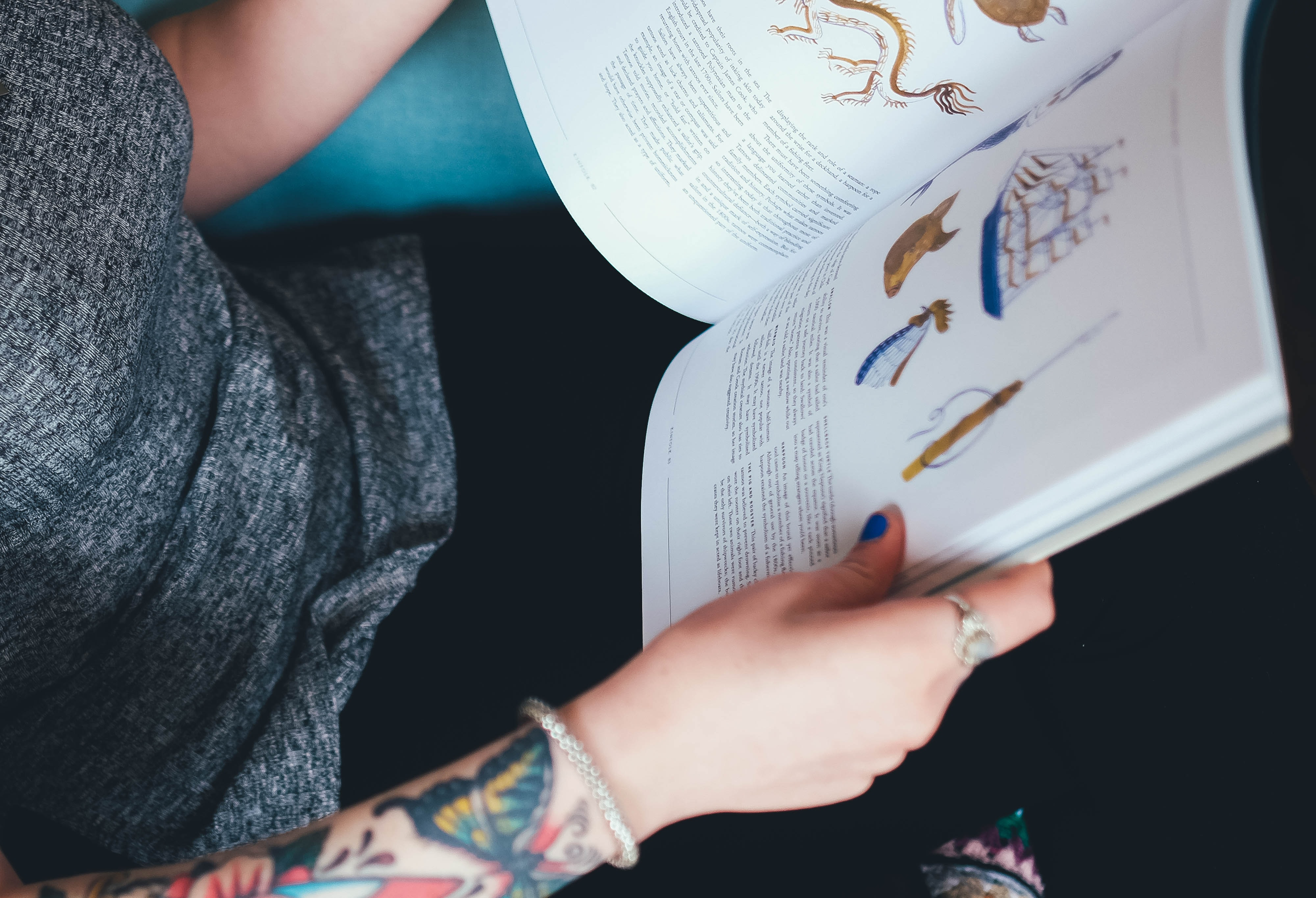 Woman with colorful butterfly tattoos sitting down, reading a book with drawings of animals and ships