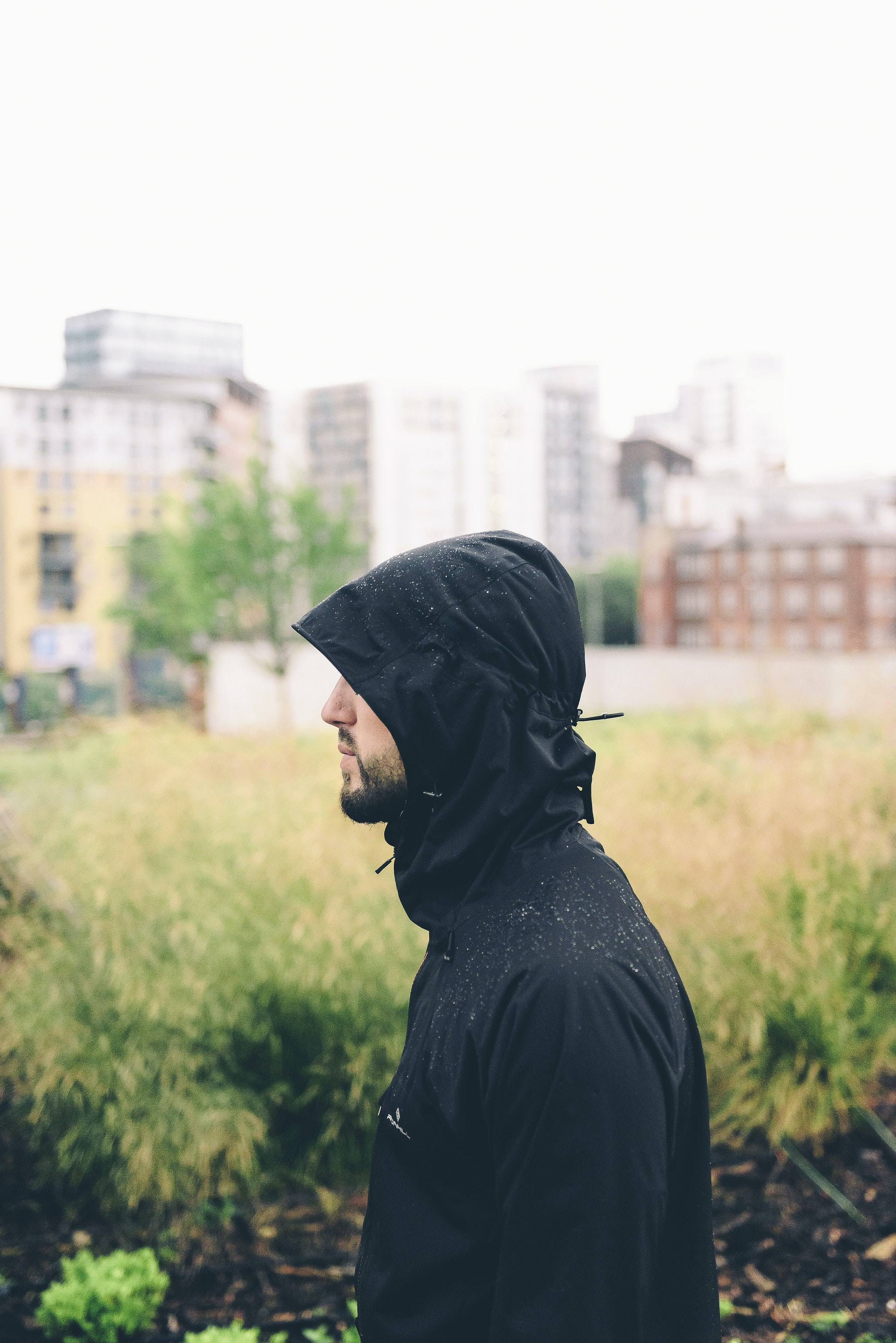 Profile of a man in a black hooded raincoat outside