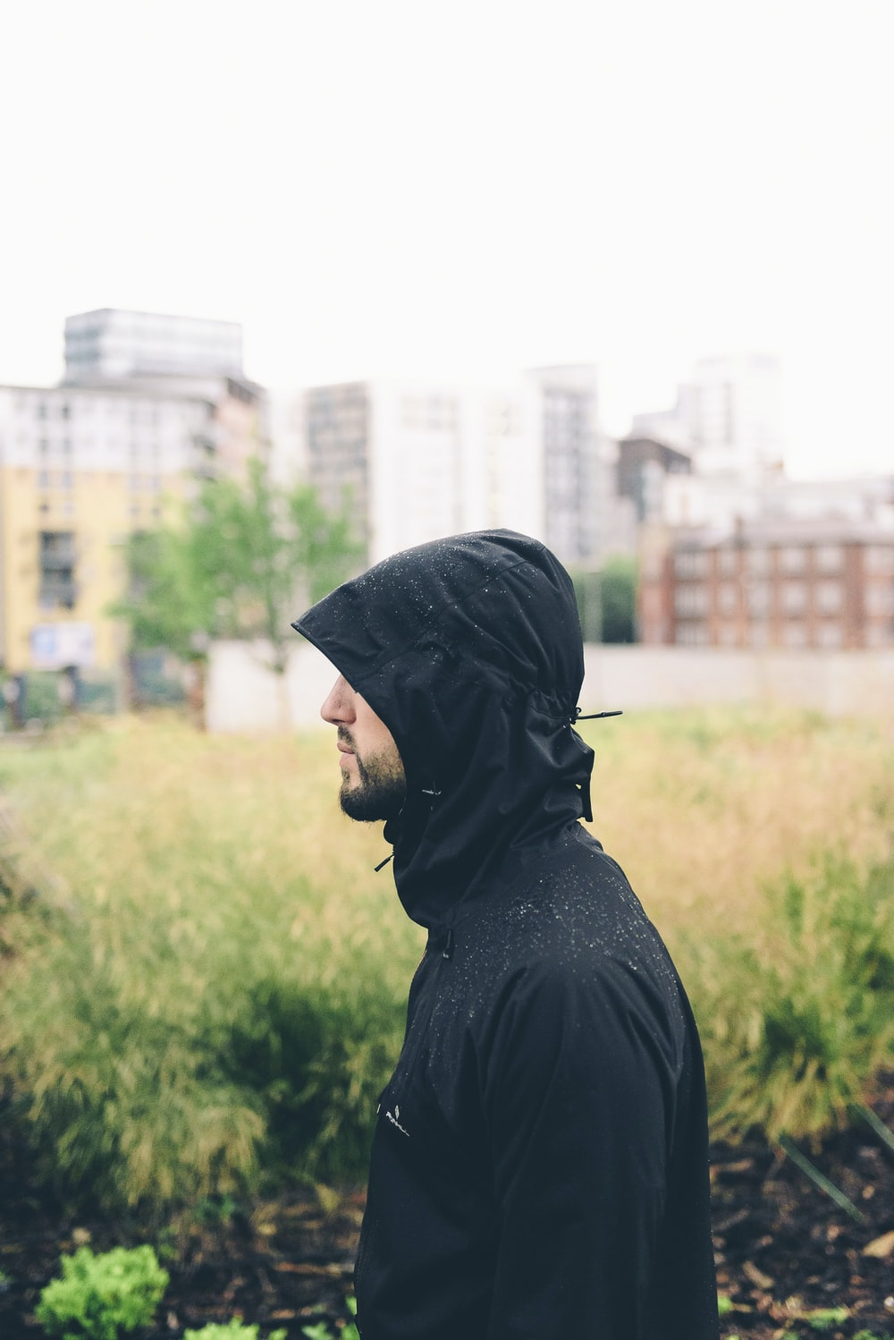 man wearing hoodie standing near grass with building background during daytime