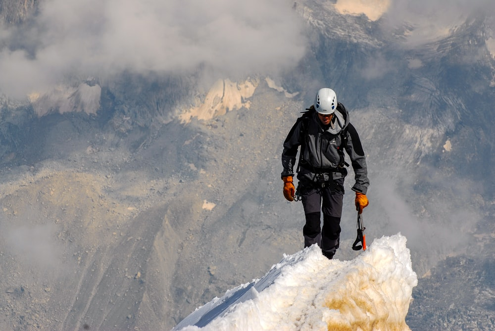 One climber making it to the top surrounded by clouds and snowy mountains