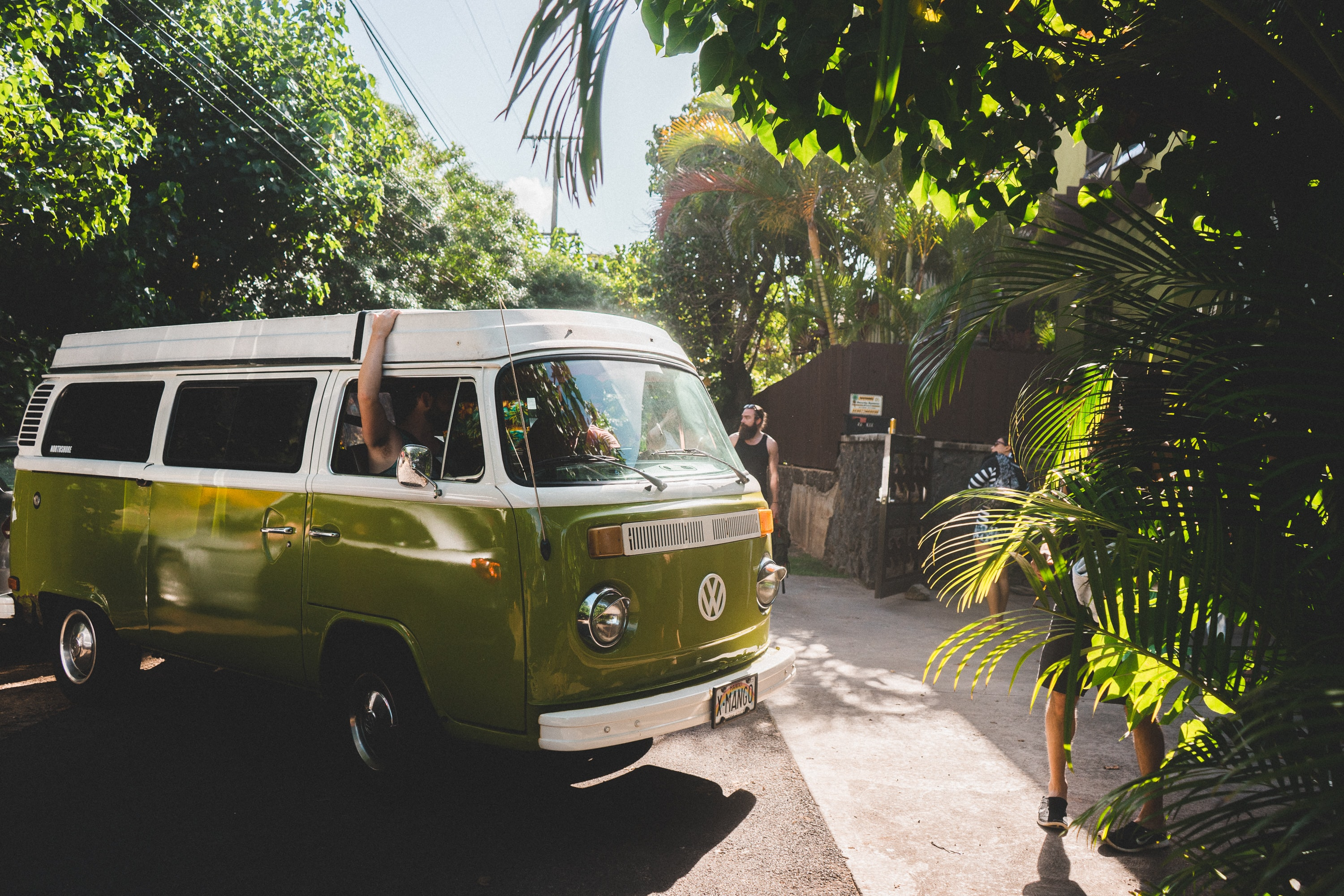A green Volkswagen bus with people inside parked by bright green trees