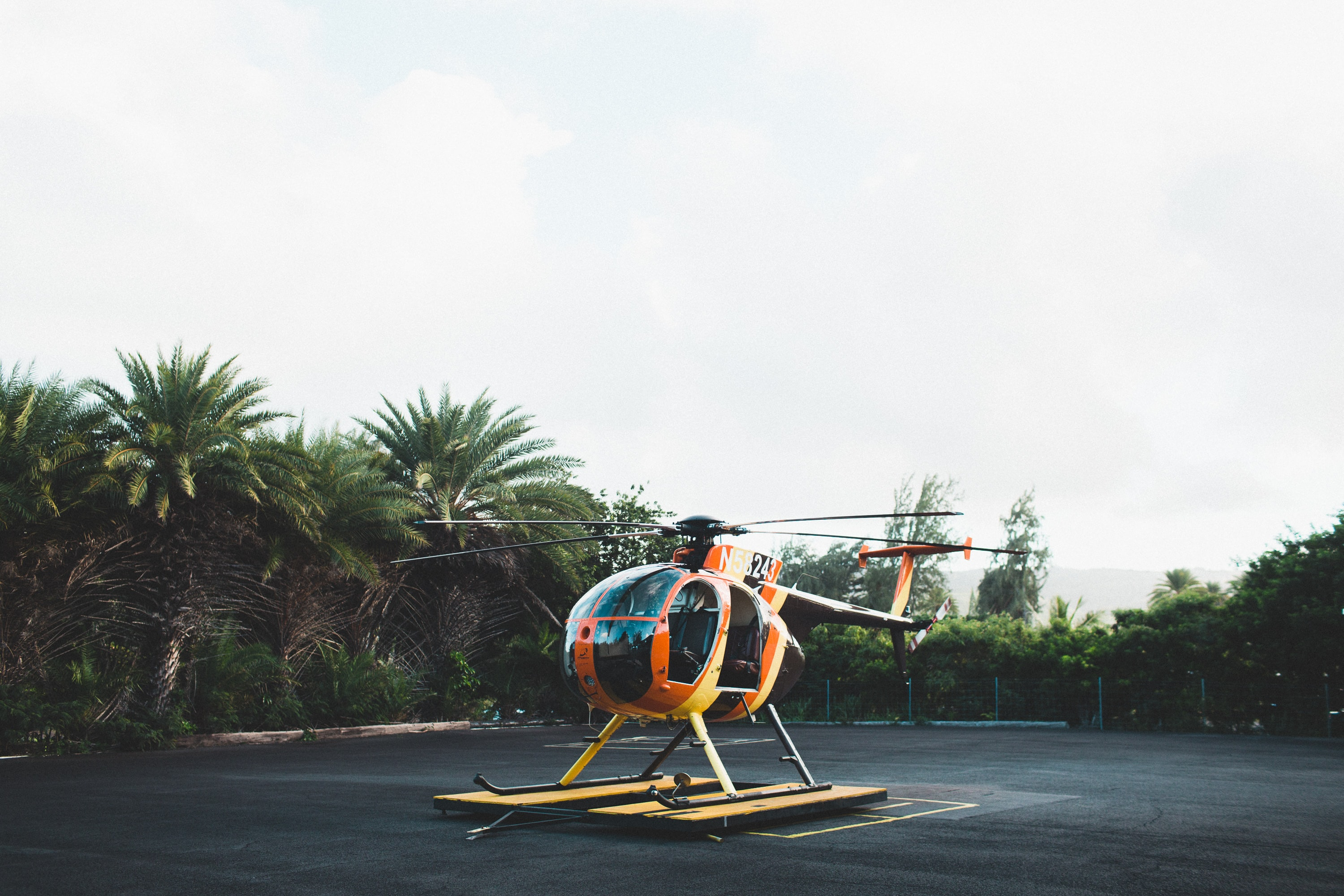 An orange helicopter on a landing pad surrounded by palm trees
