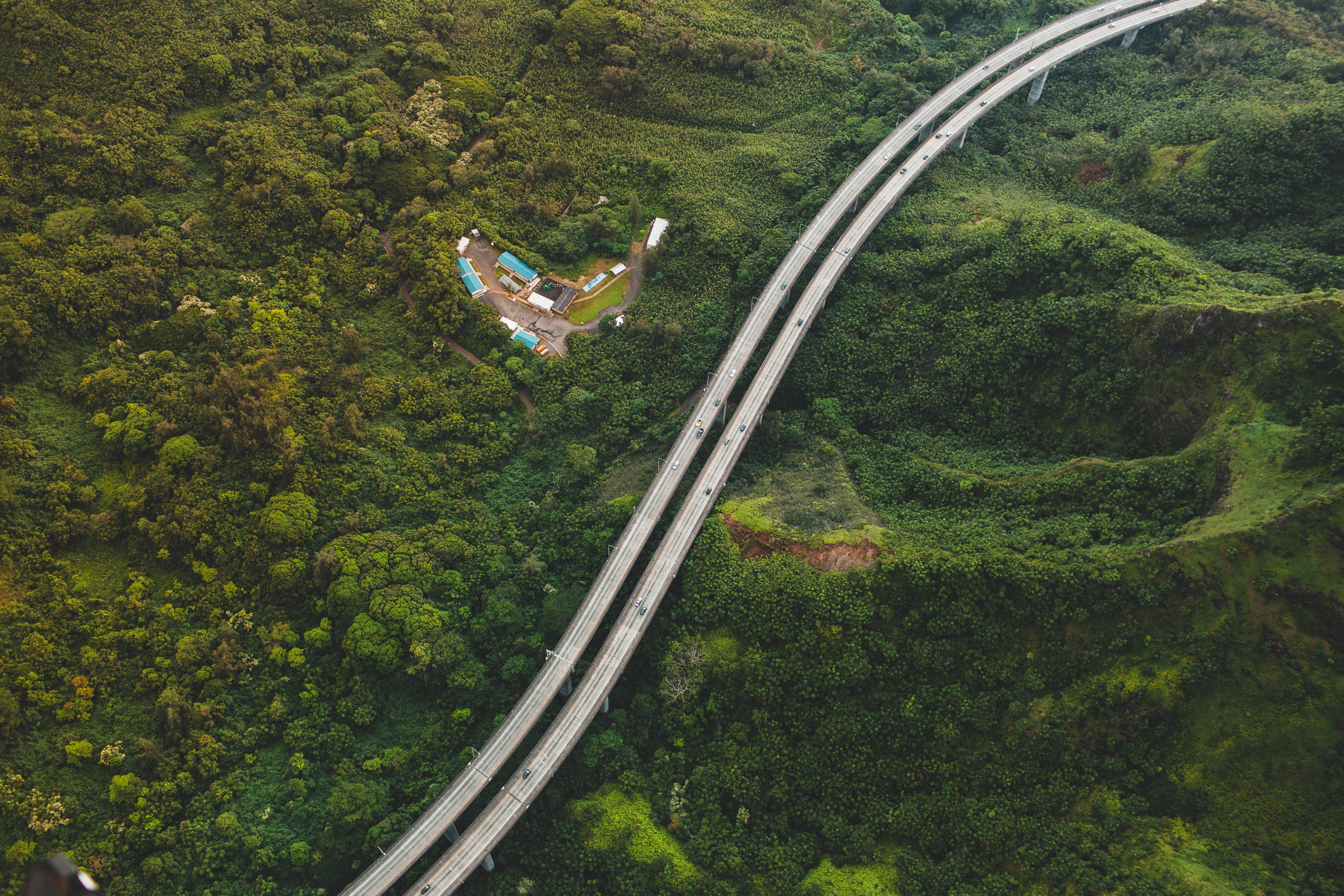 A drone shot of a two-lane road on forested hills