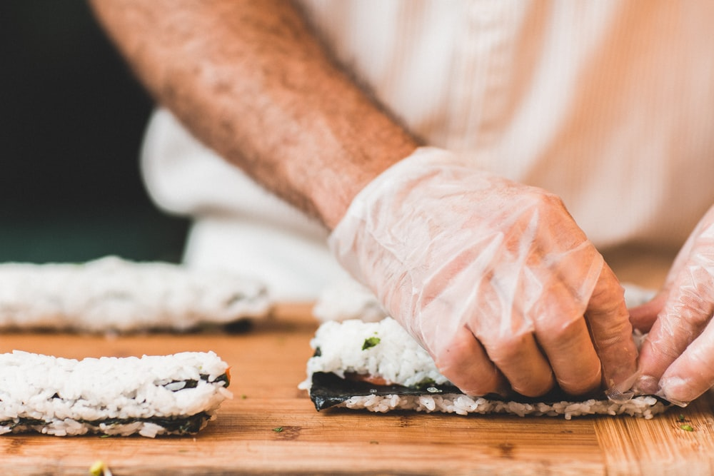 Close-up of a man preparing sushi on a wooden surface