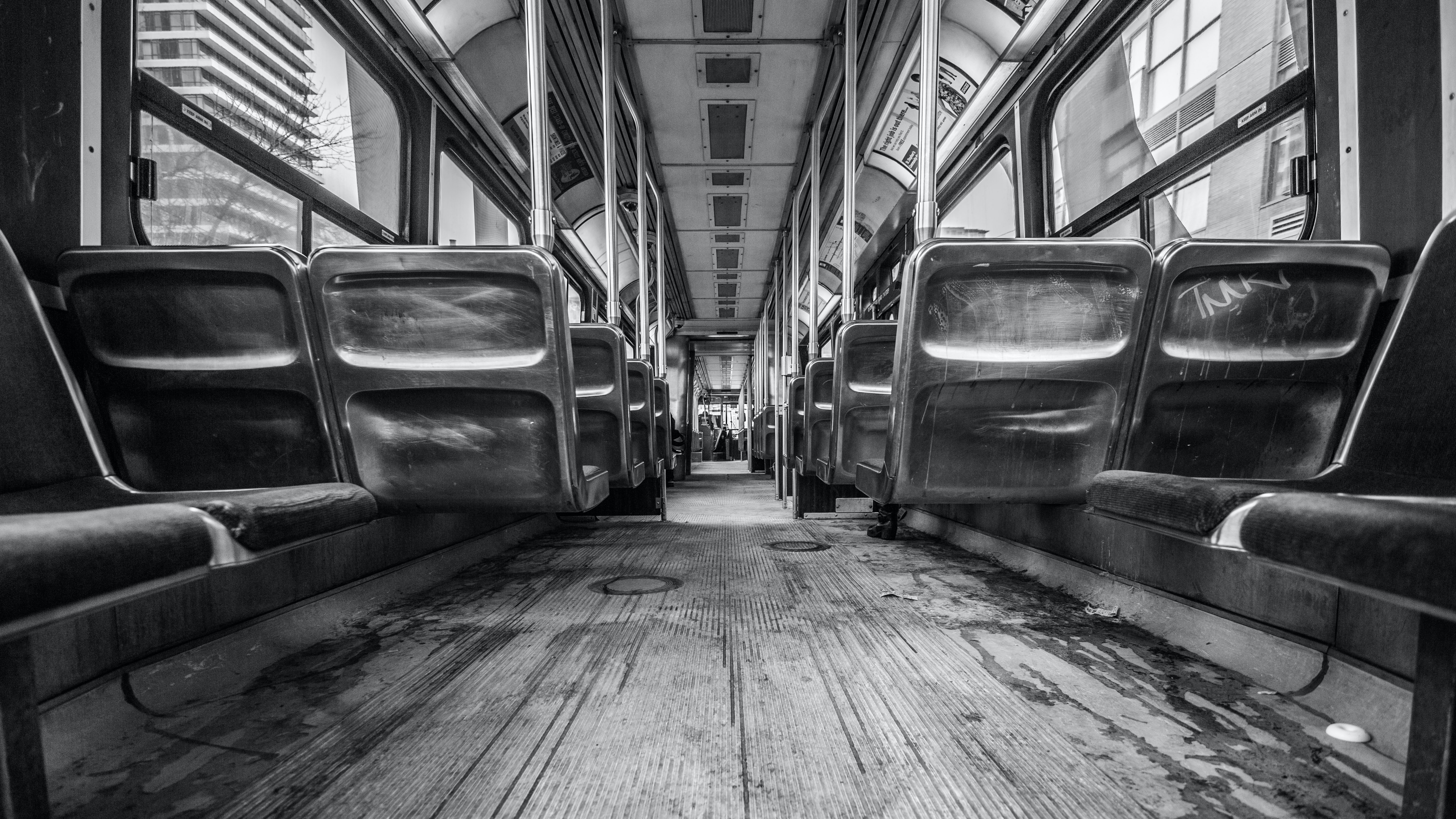 Black and white shot of carriage interior with dirty floor and seating
