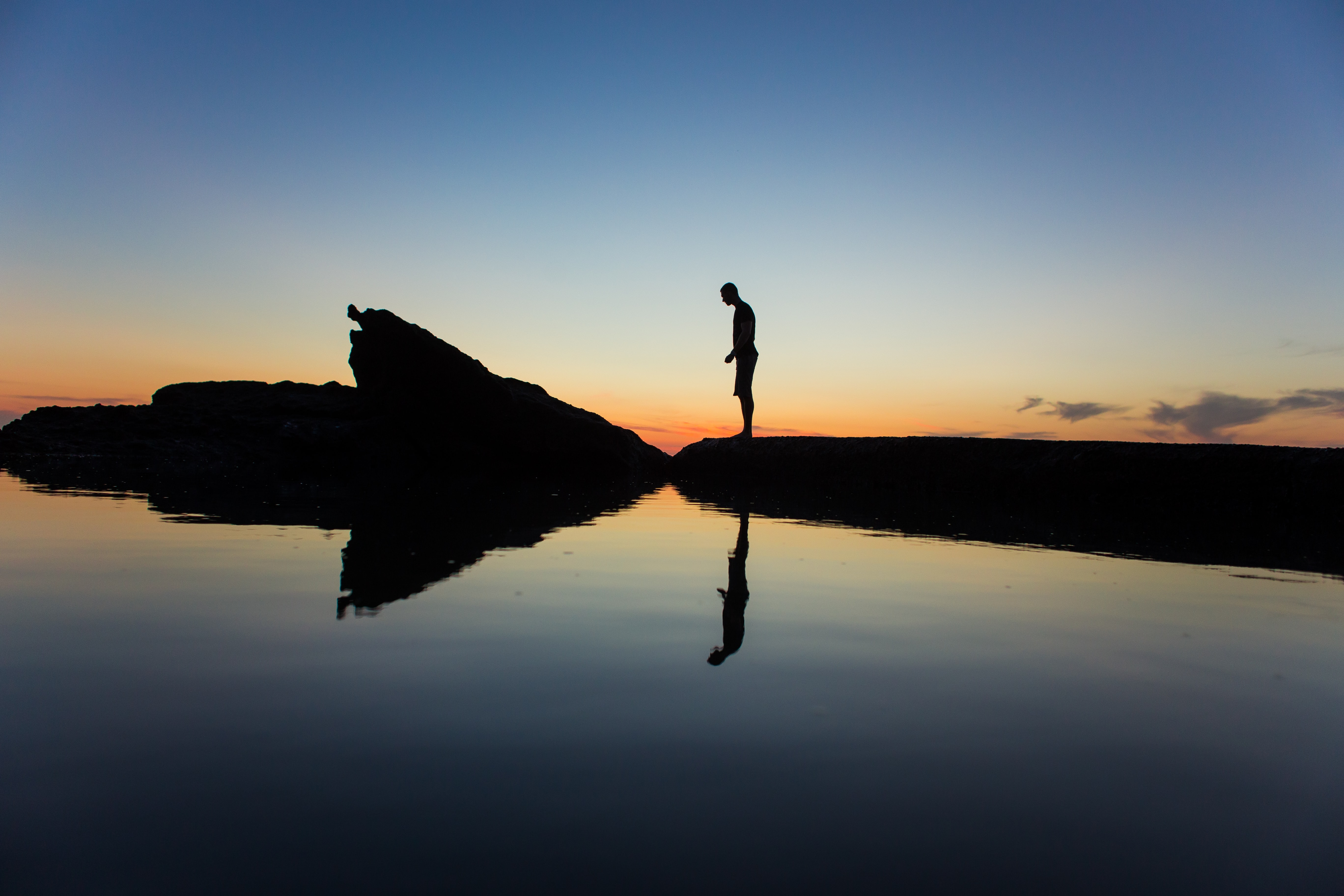Man silhouette standing on the rock with reflection at Virginia Beach after sunset