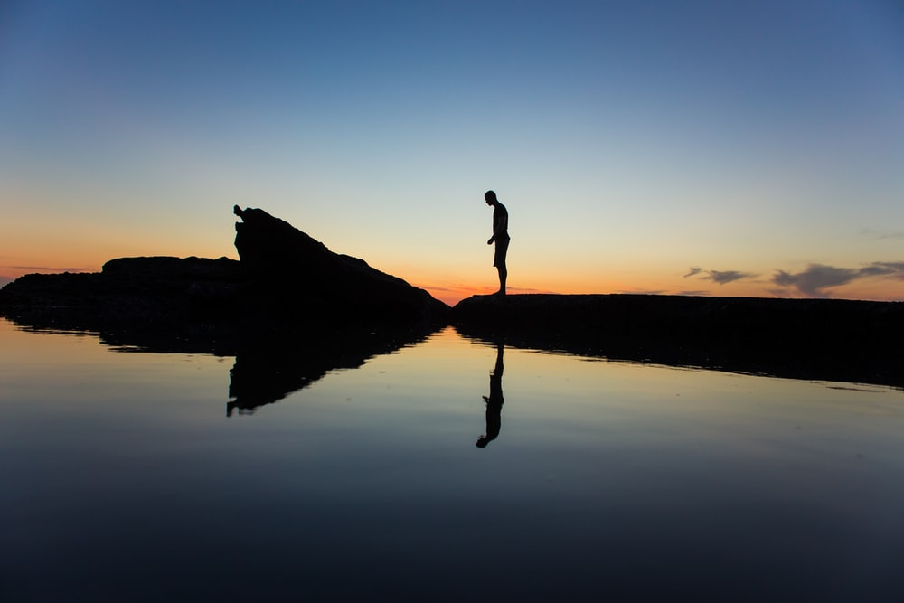 silhouette of man standing on land near body of water with reflection