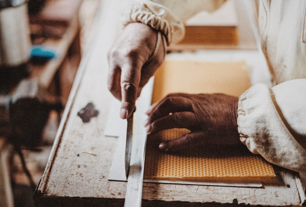 person holding chisel while carving wood