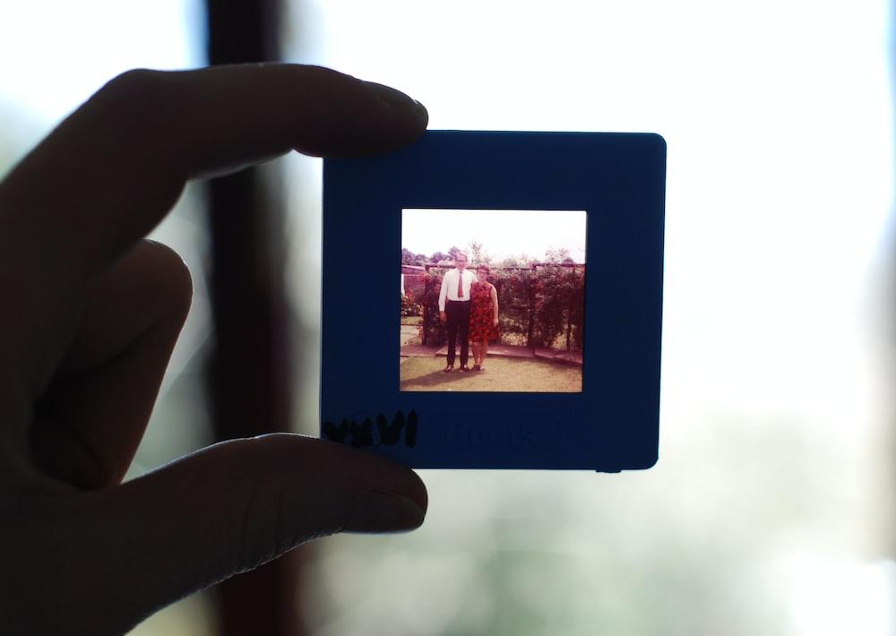 person holding square black photo frame