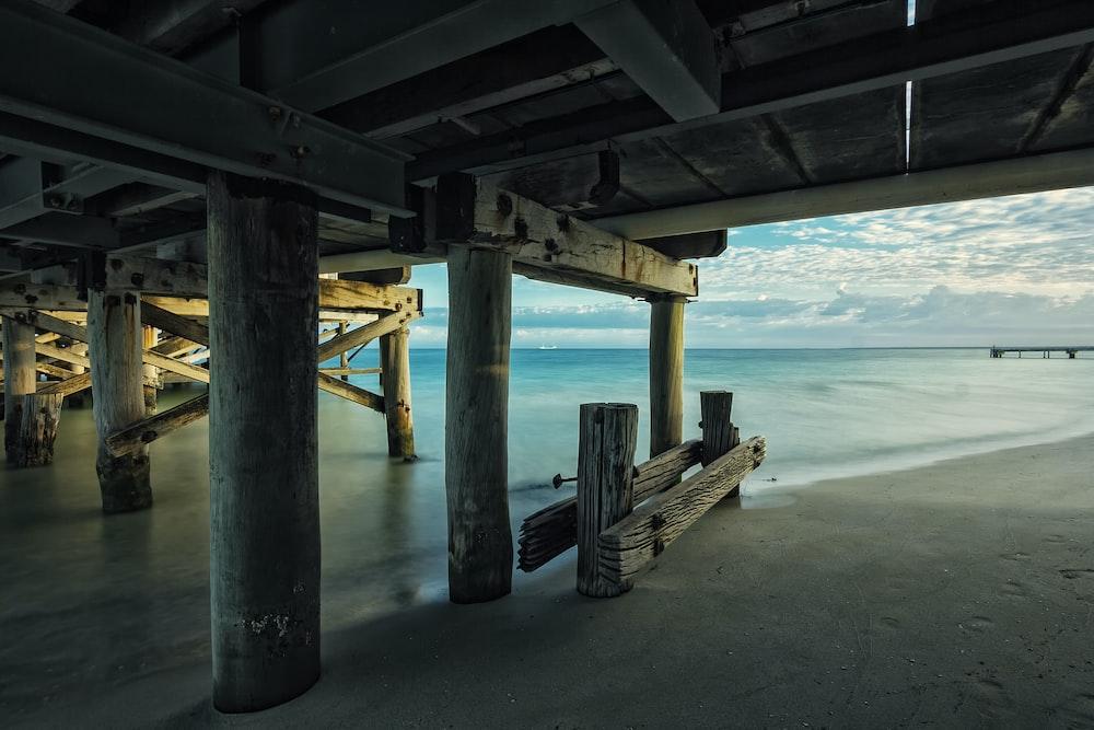 brown wooden footbridge under body of water