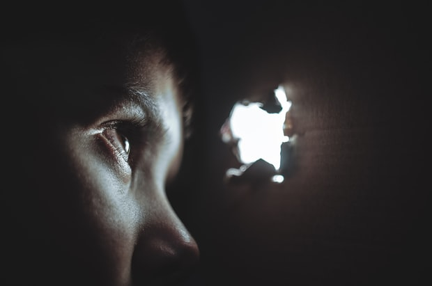 Picture of young face in a dark room, peering out at the world through a small hole