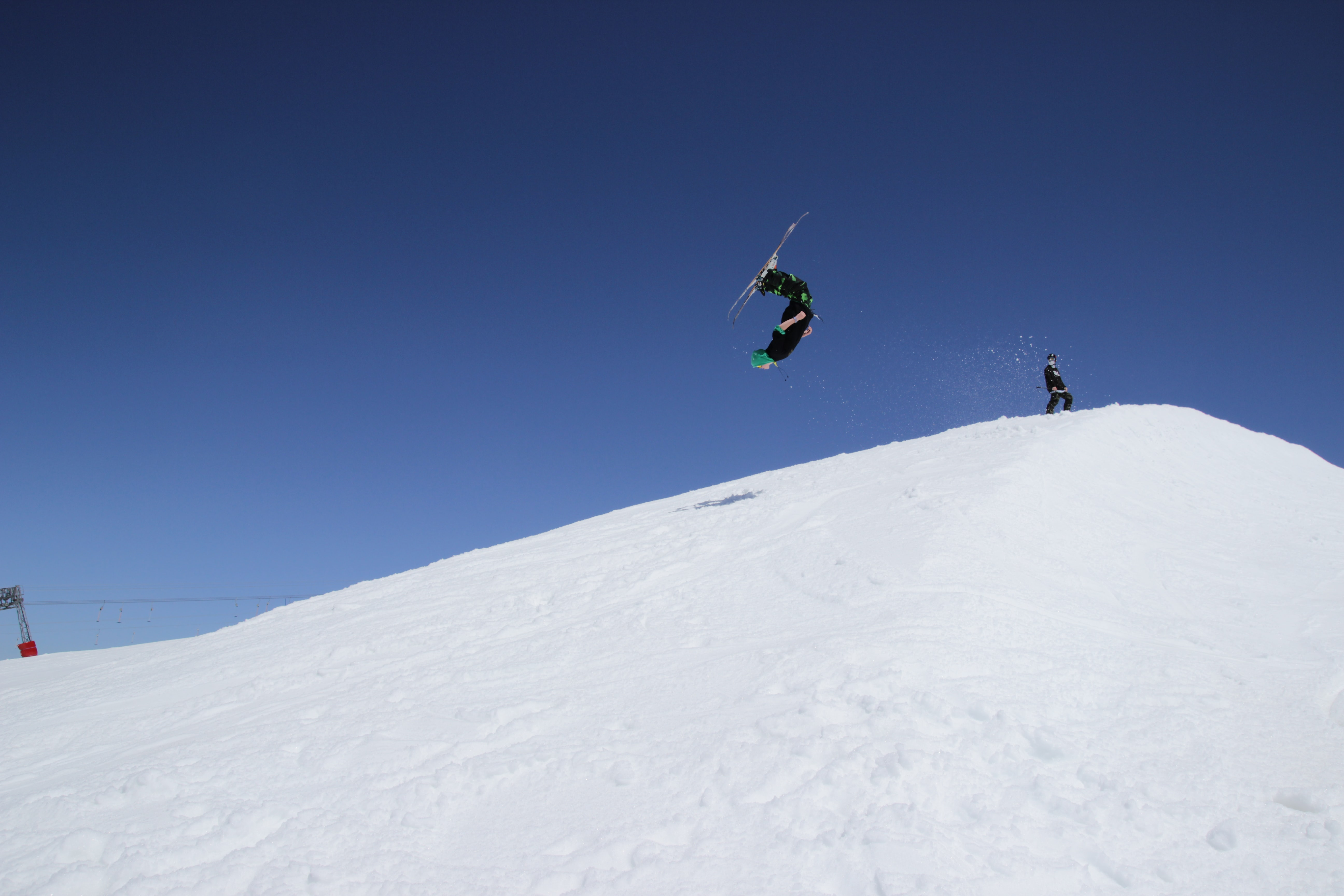 A skier upside down mid-flip over a snowy hill against a clear, blue sky