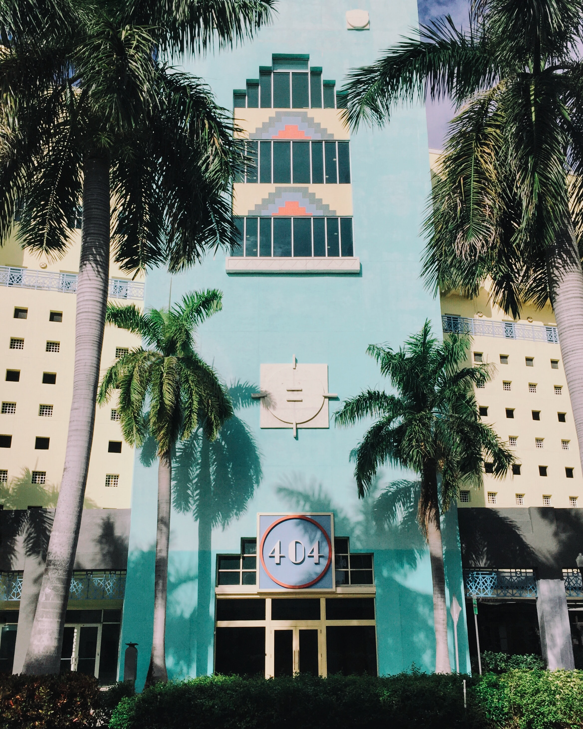 blue 404 concrete building with coconut trees in frontt