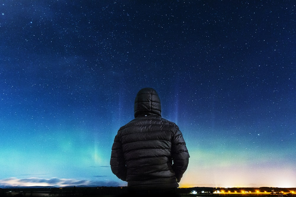 man in black bubble hoodie looking at the stars