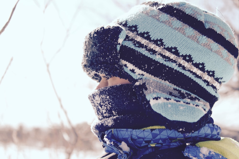 person wearing black and teal striped hat at snowtime