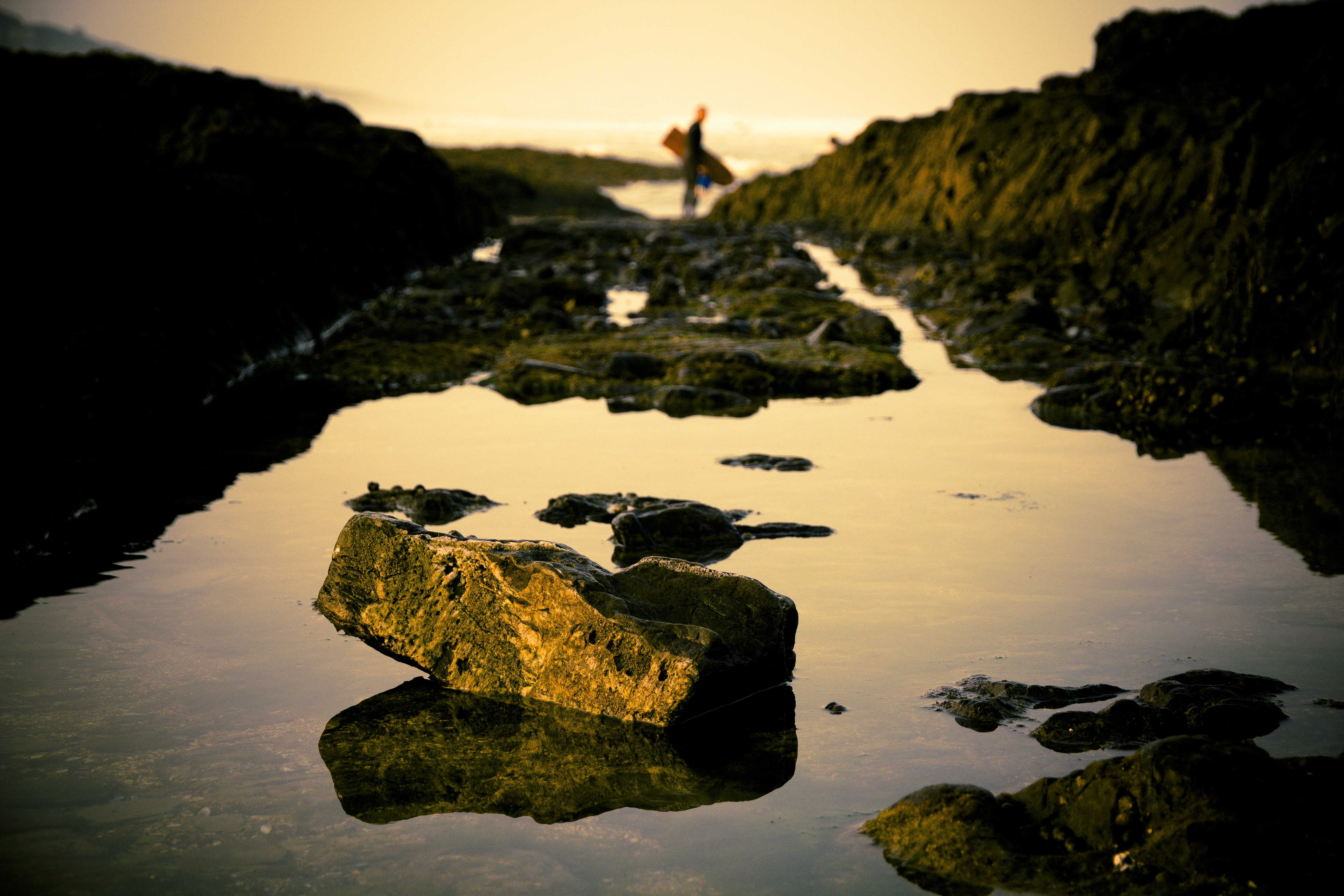 Coastal rocks with surfer in the background at Croyde Beach
