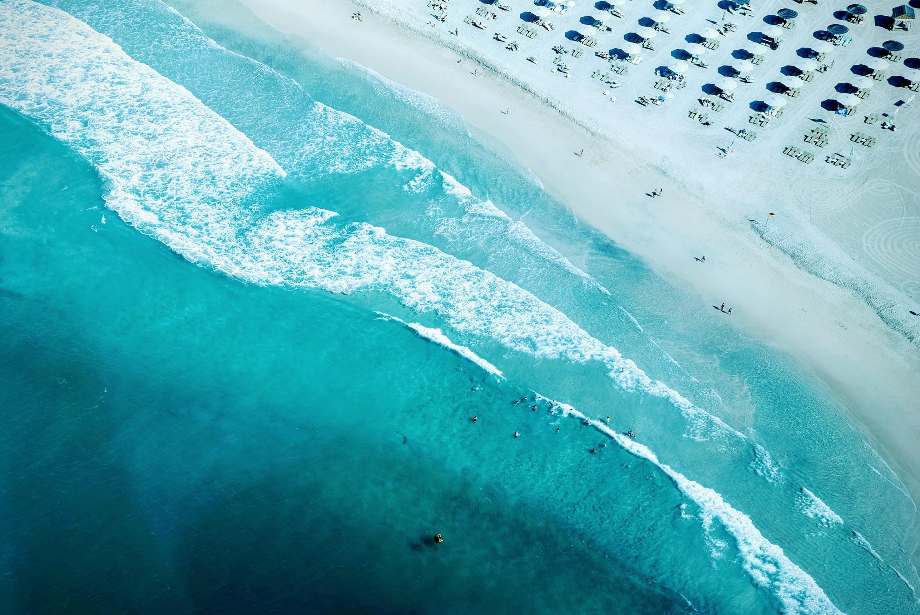 Clear blue ocean tide waves washing into sanding beach in Dubai