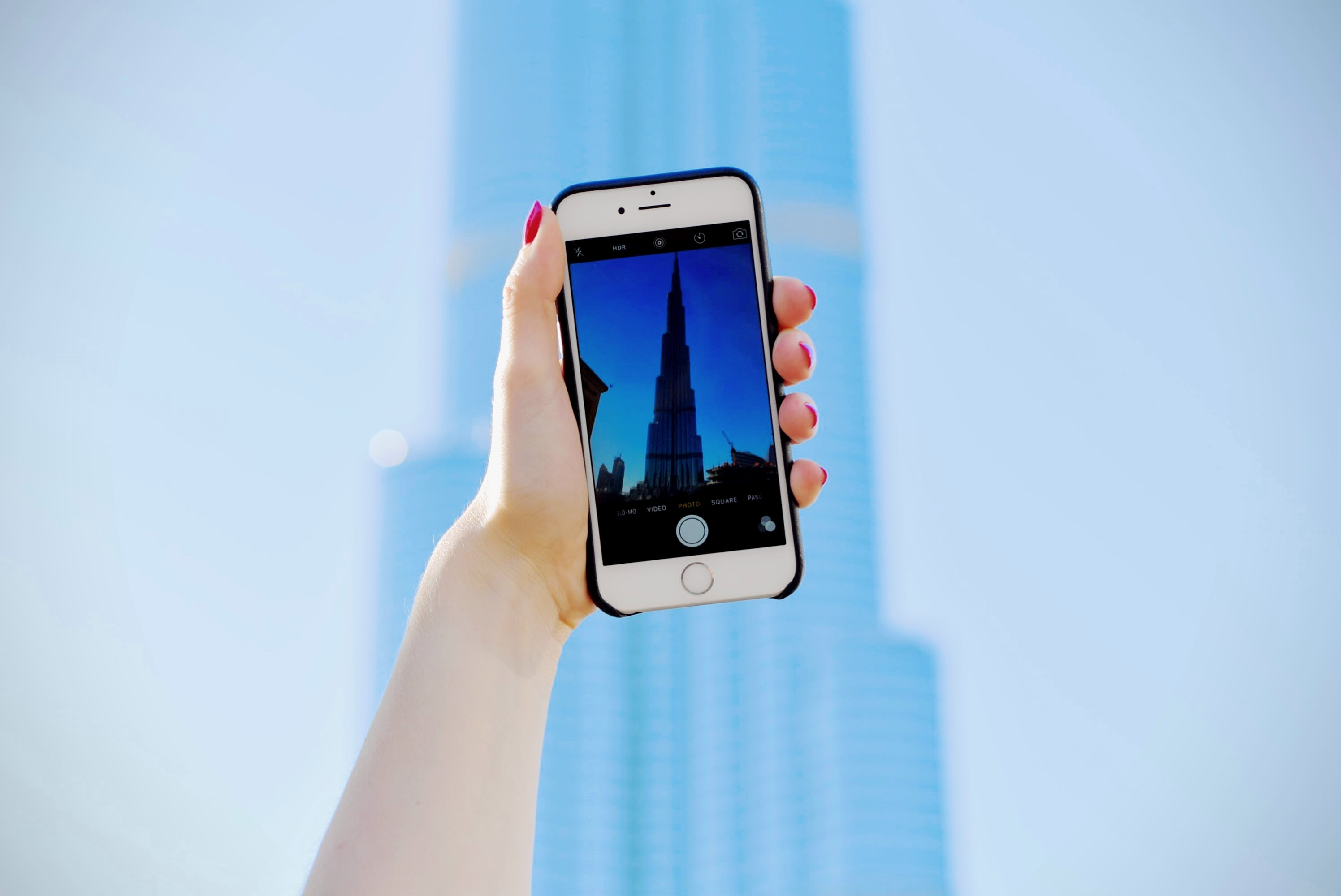 A woman's hand holding an iPhone with its camera pointed at Burj Khalifa in Dubai