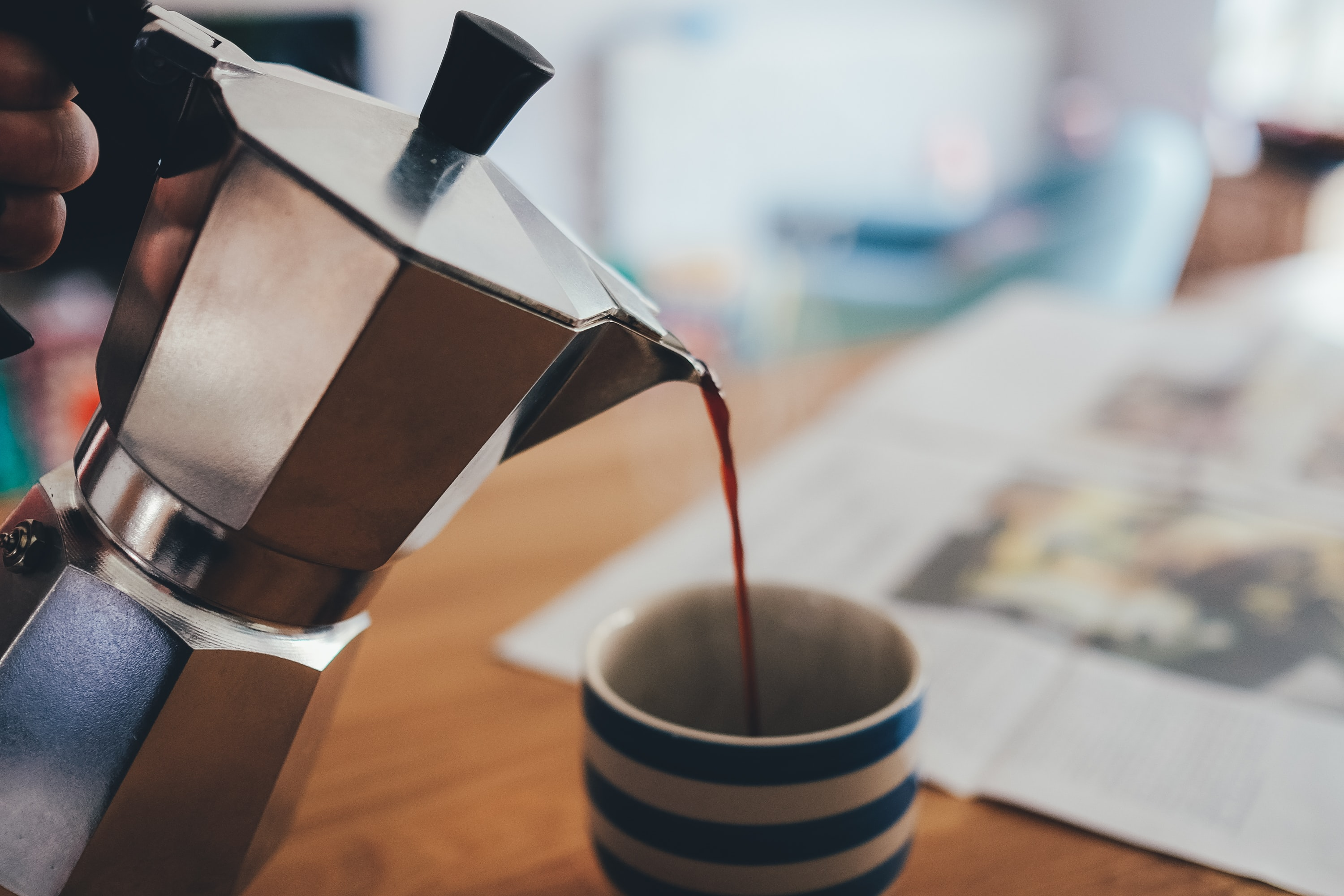 A person pouring coffee from a steel kettle into a mug