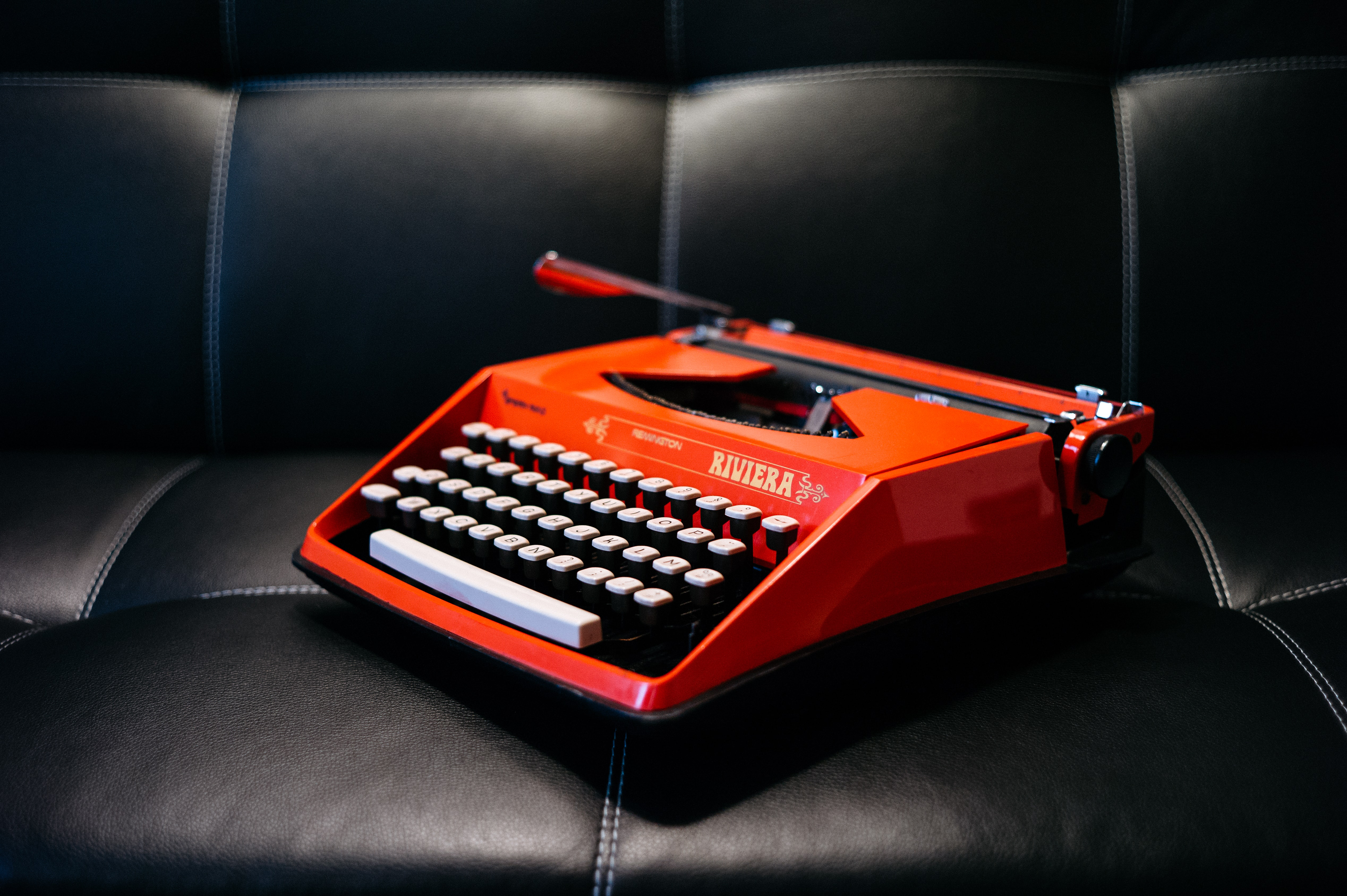 A red Riviera typewriter on a black leather couch