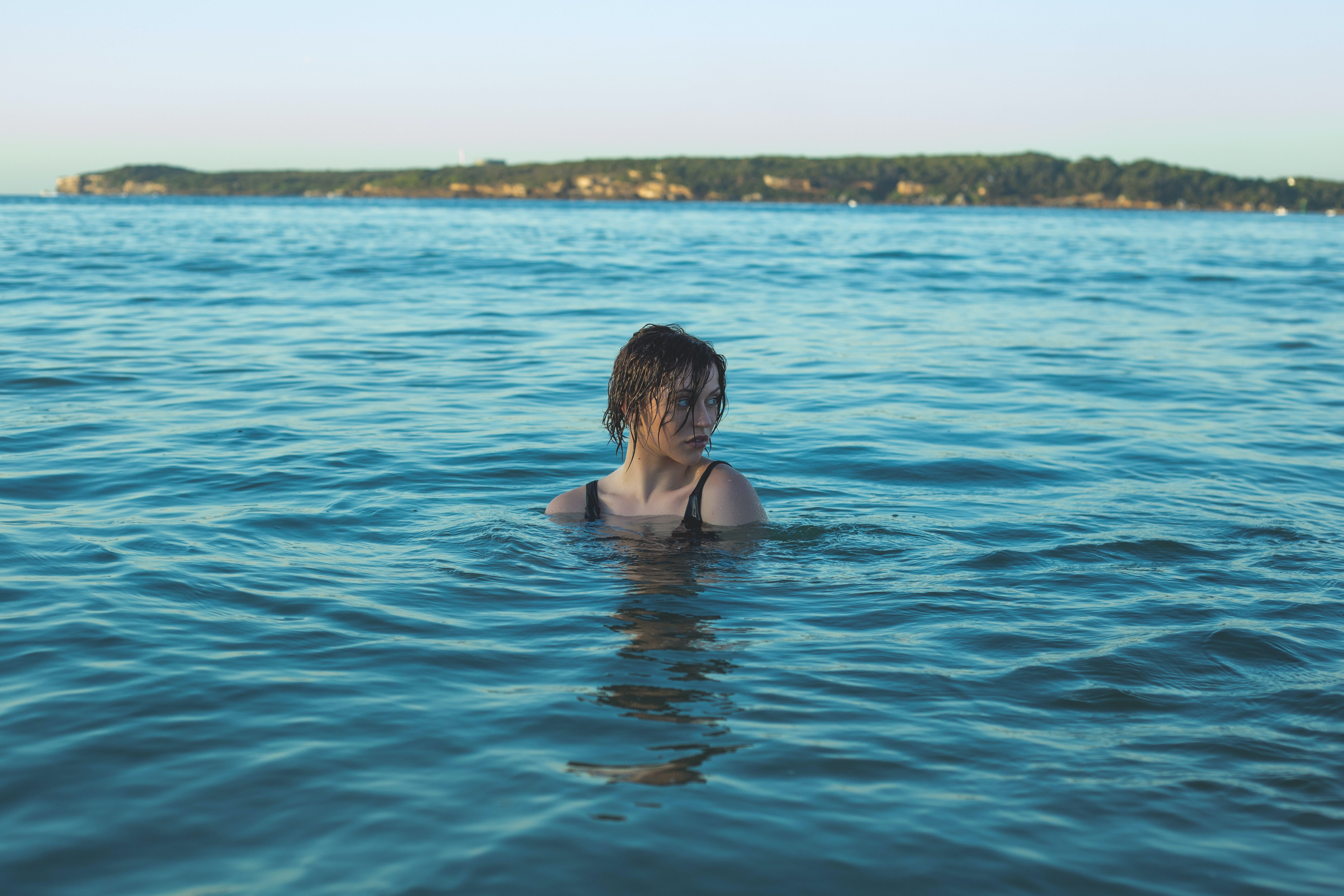 A young woman swimming in the sea with the coast visible on the horizon