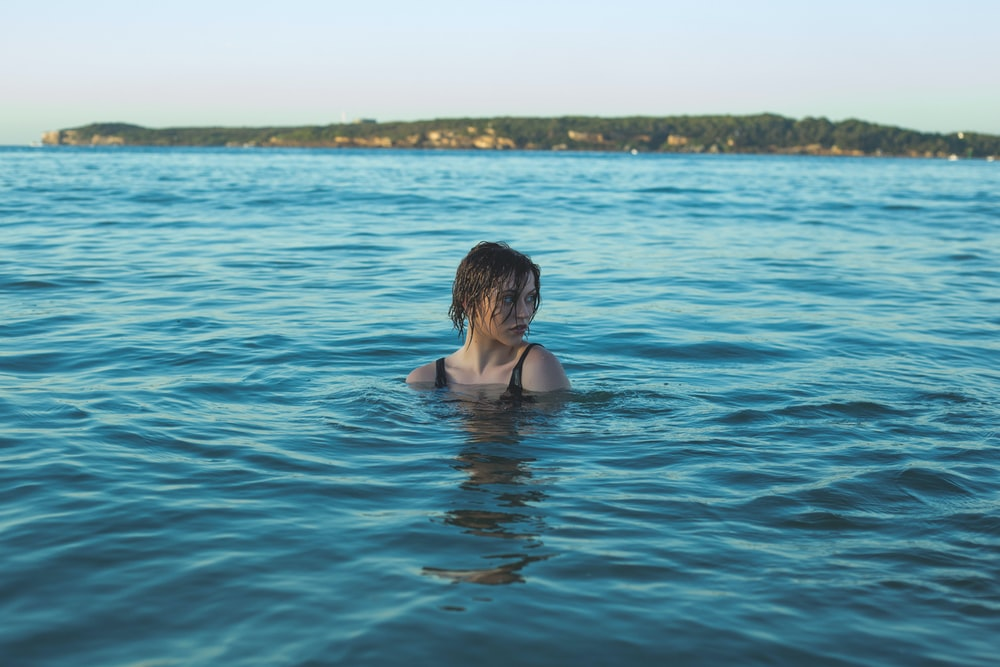 photography of woman in black swimming wear soaked in sea