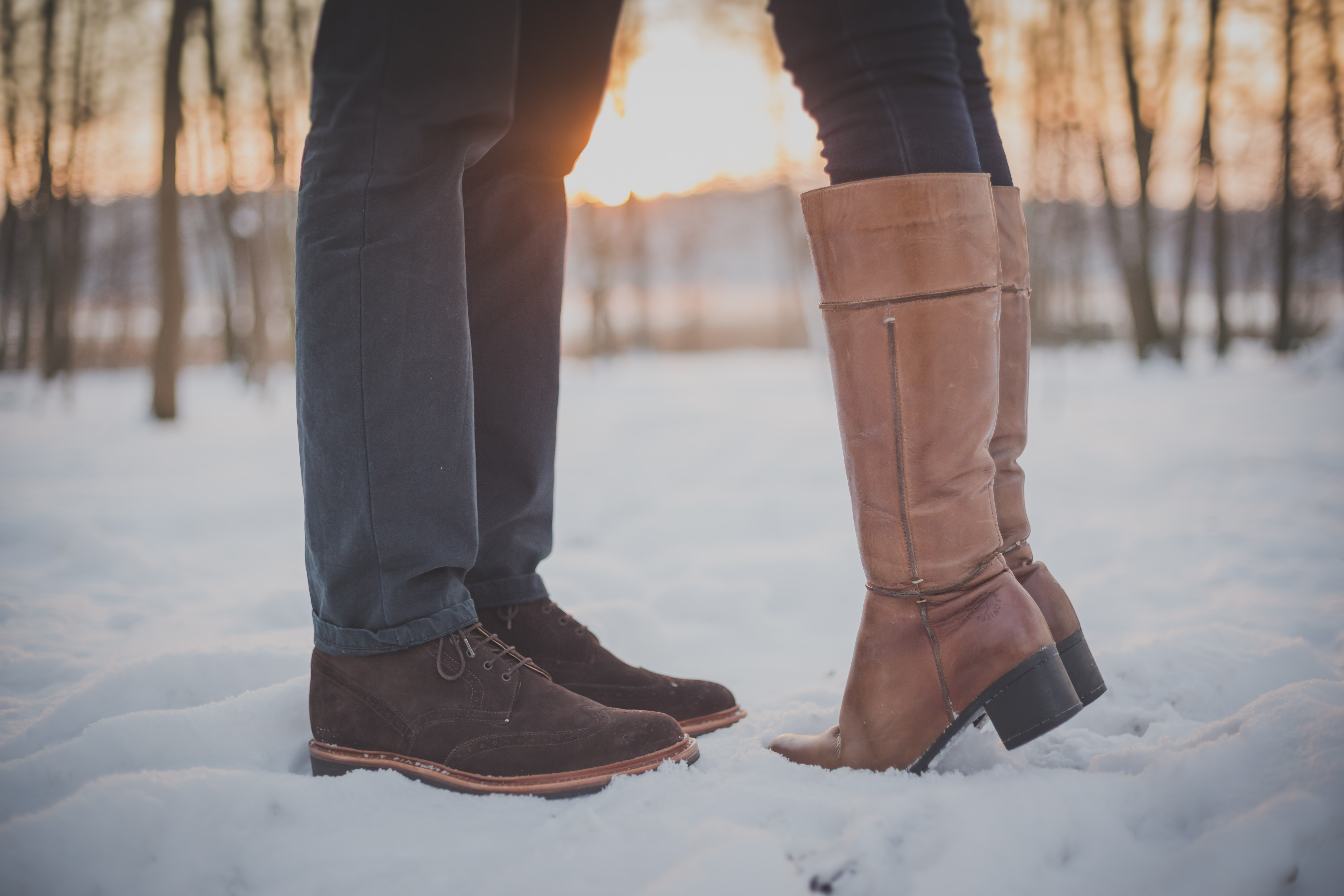 On a snowy day, a woman in boots rises on tip-toe to kiss a man