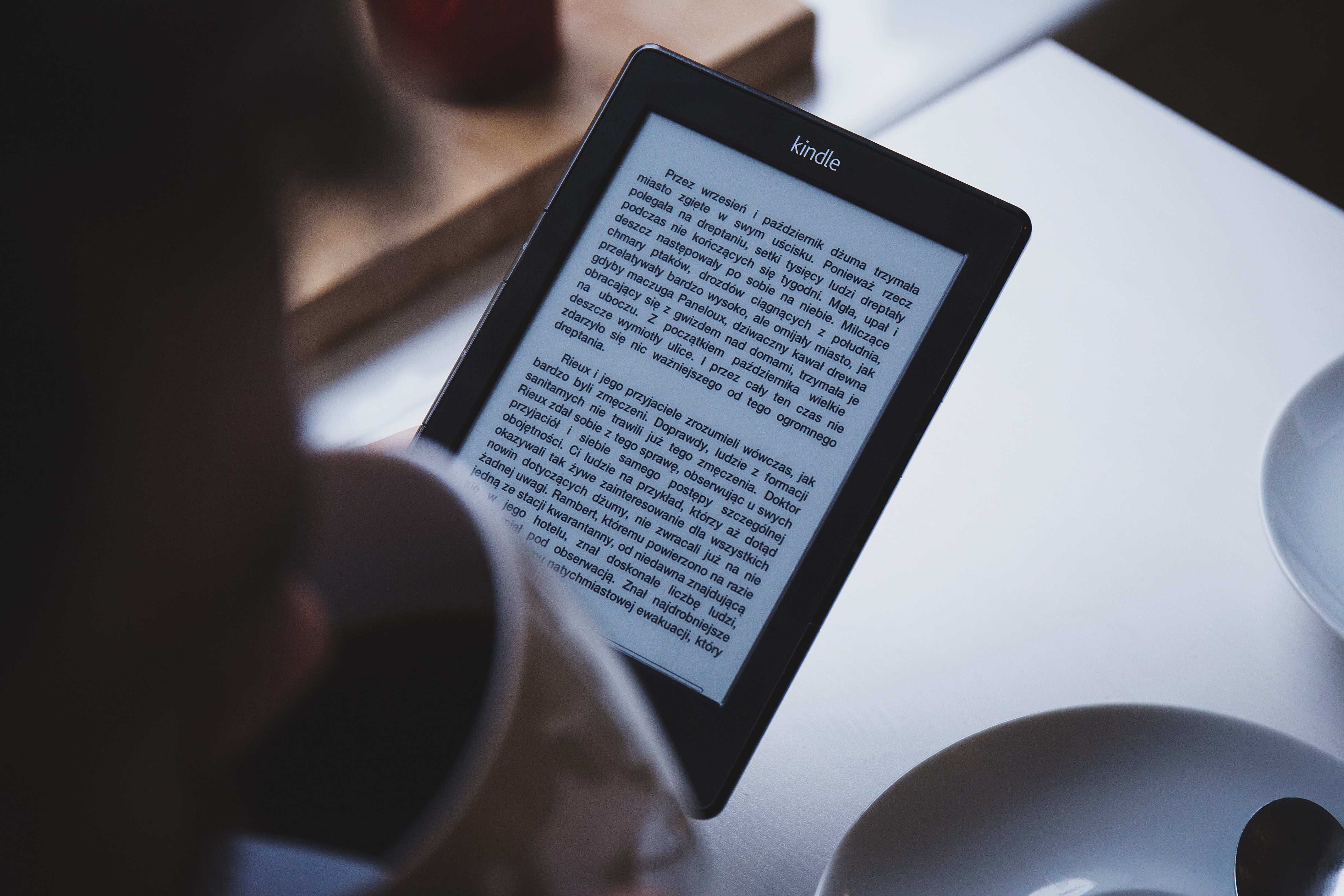 A person reading a book on a Kindle while drinking coffee