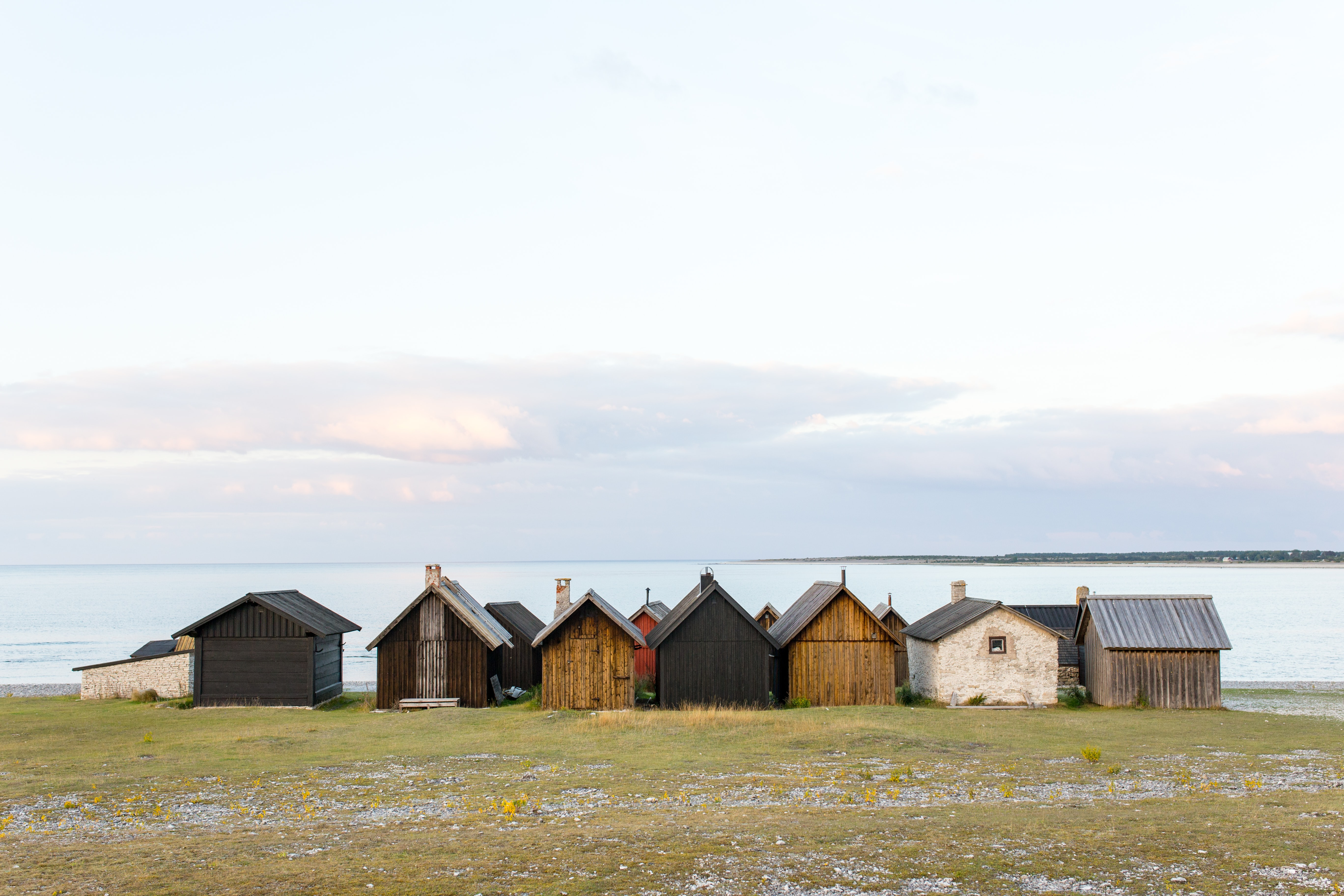 landscape photography of shacks near body of water