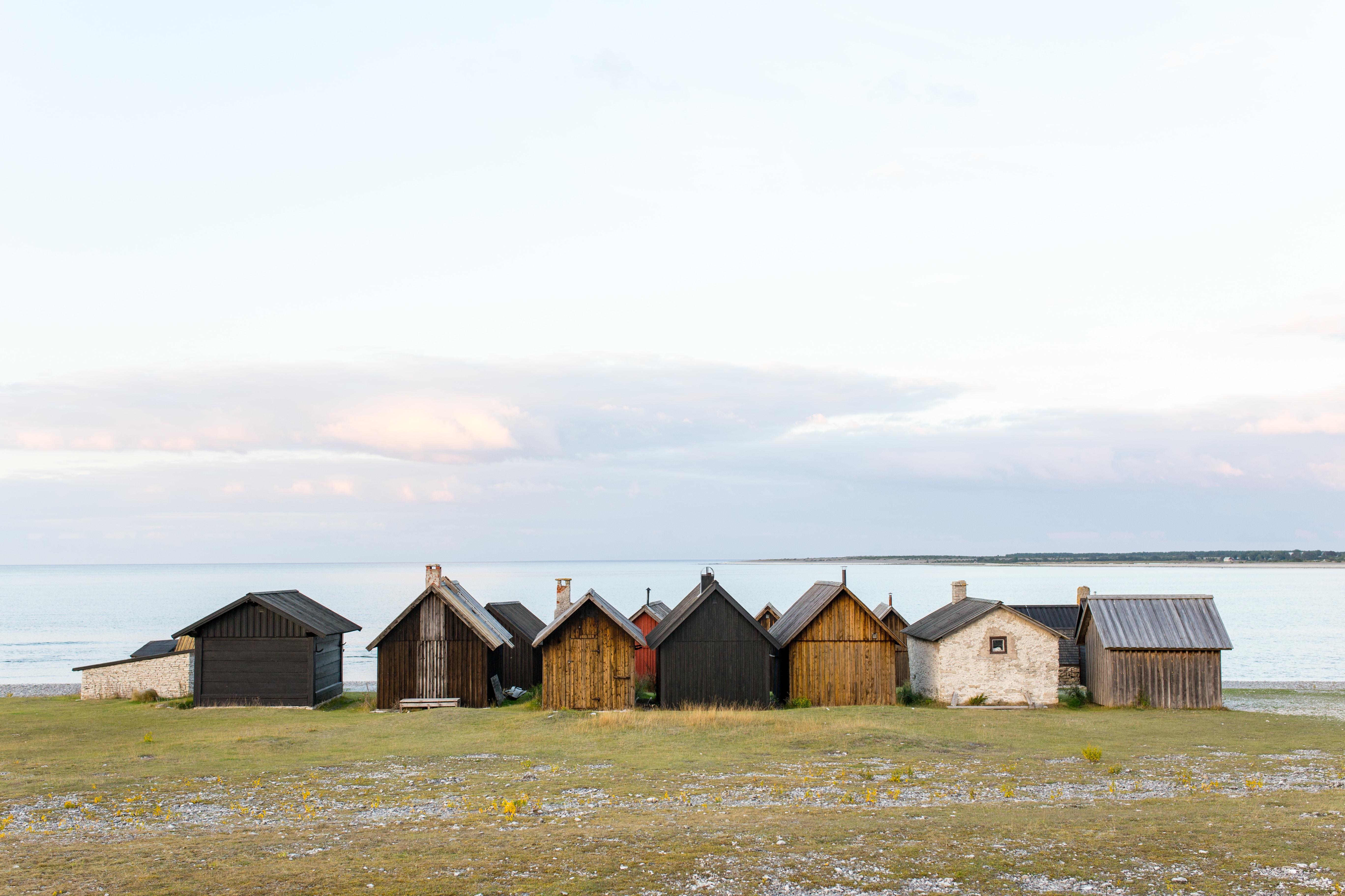 landscape photography of shacks near body of water