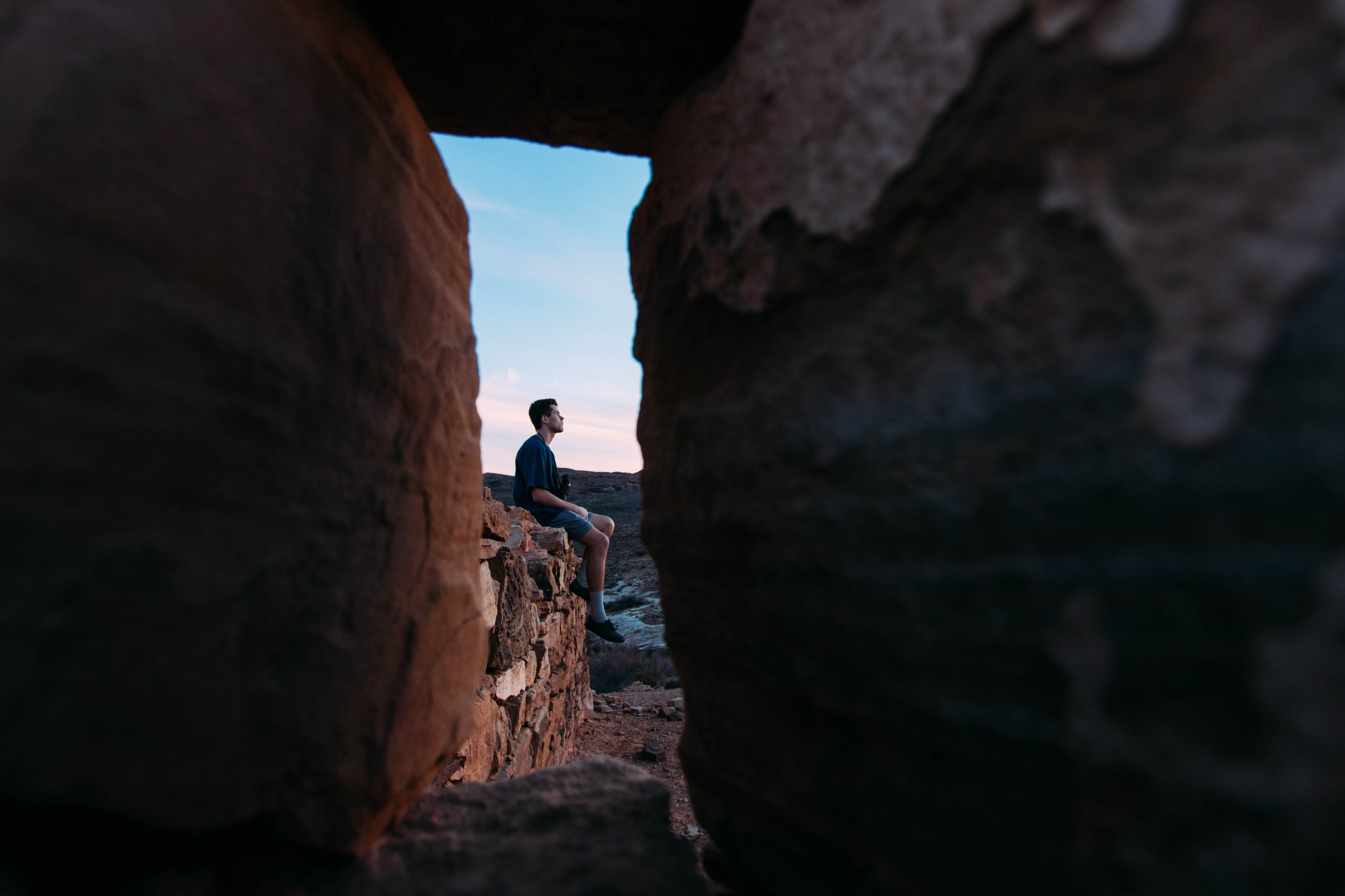 A man sitting on red rocks seen through a gap in a rock formation