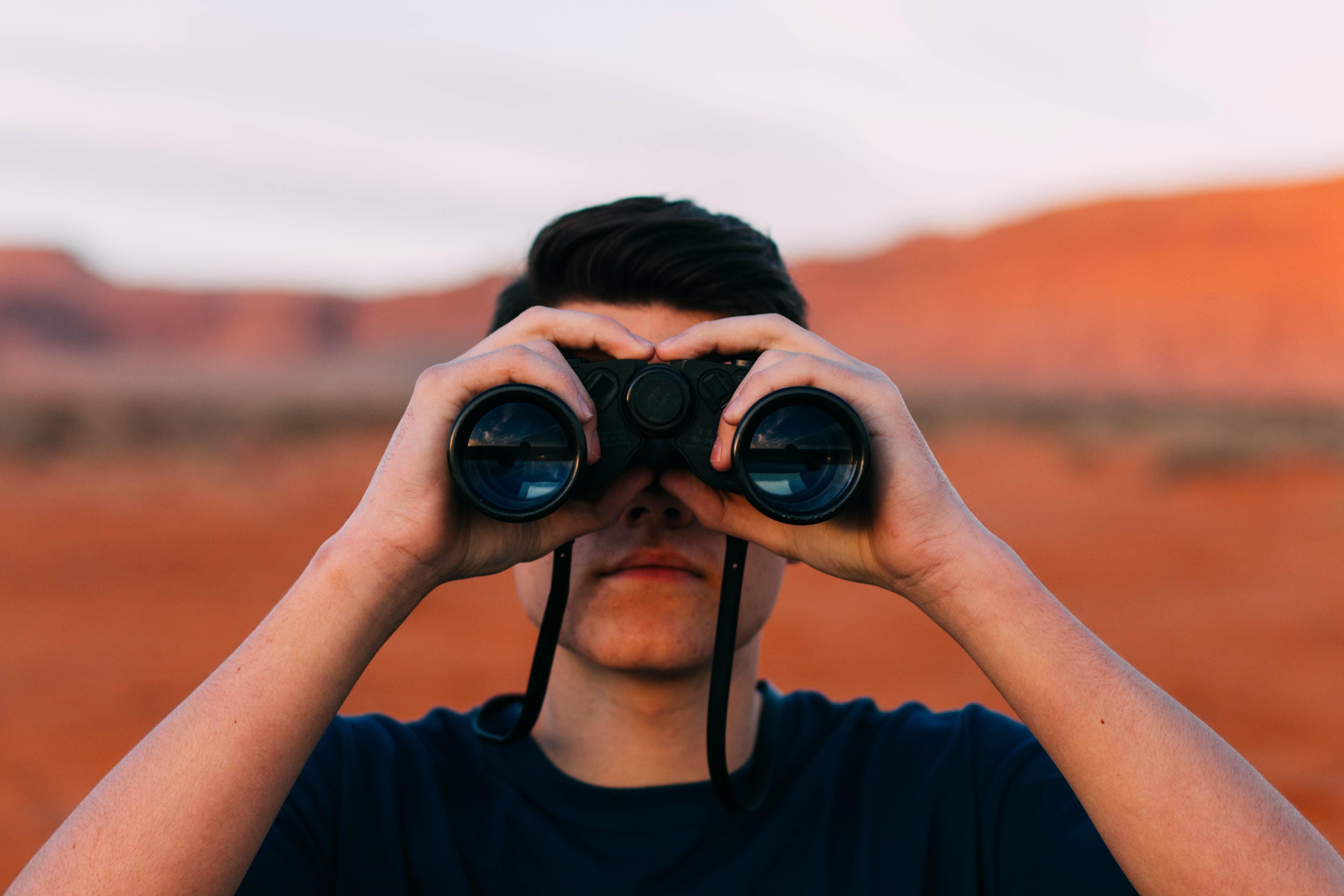 A man looking through binoculars in the desert