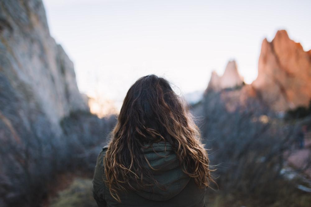 woman facing mountains at daytime