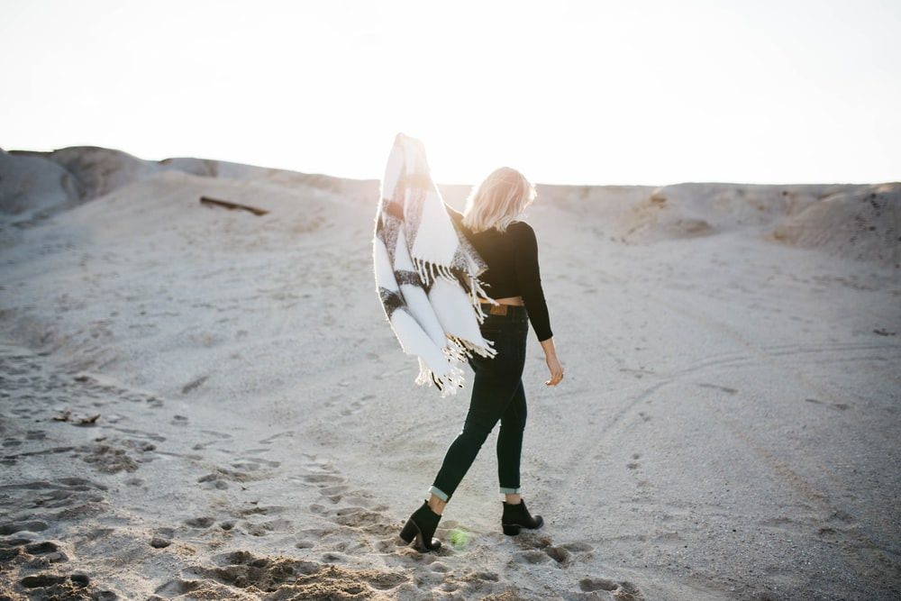woman standing on gray sand under sunrise