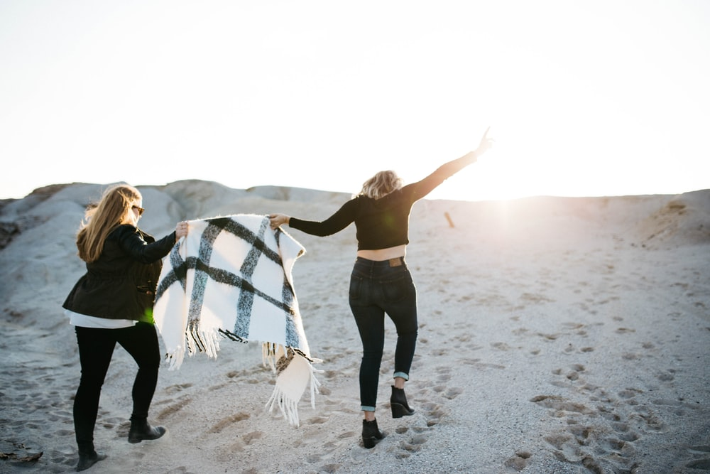 vignette photography of two woman holding scarf walking on sand