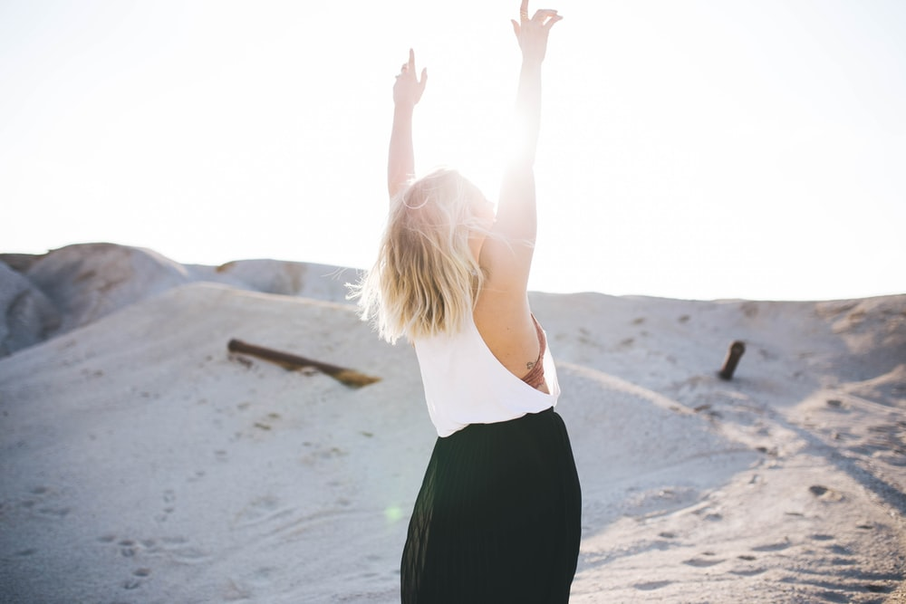 woman standing on the desert while her hands up