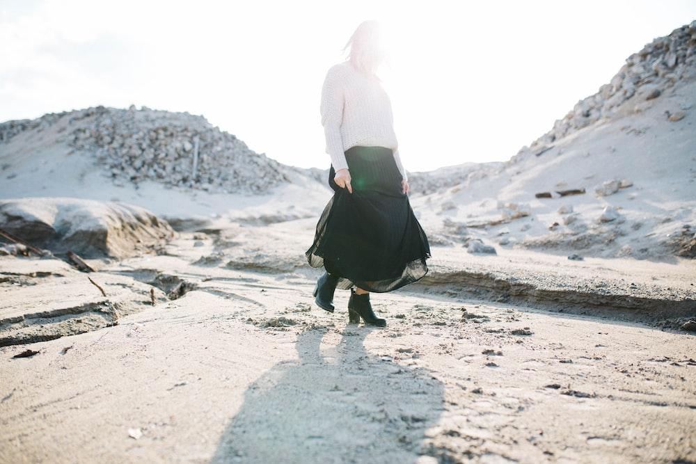 woman in black skirt walking on gray flooring