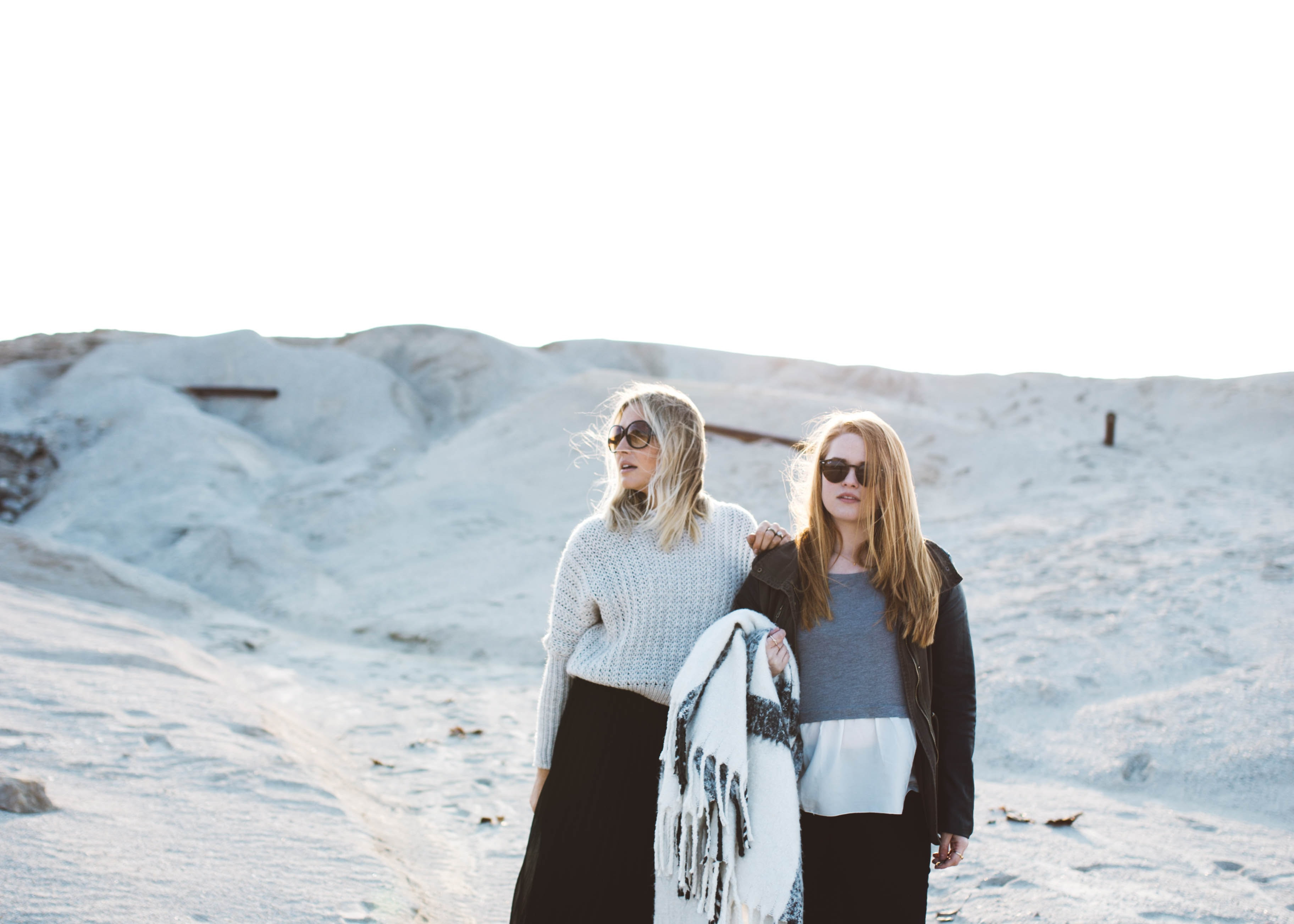 A blonde woman with her redhead daughter, both wearing sunglasses whilst stood on the sand dunes of Joplin