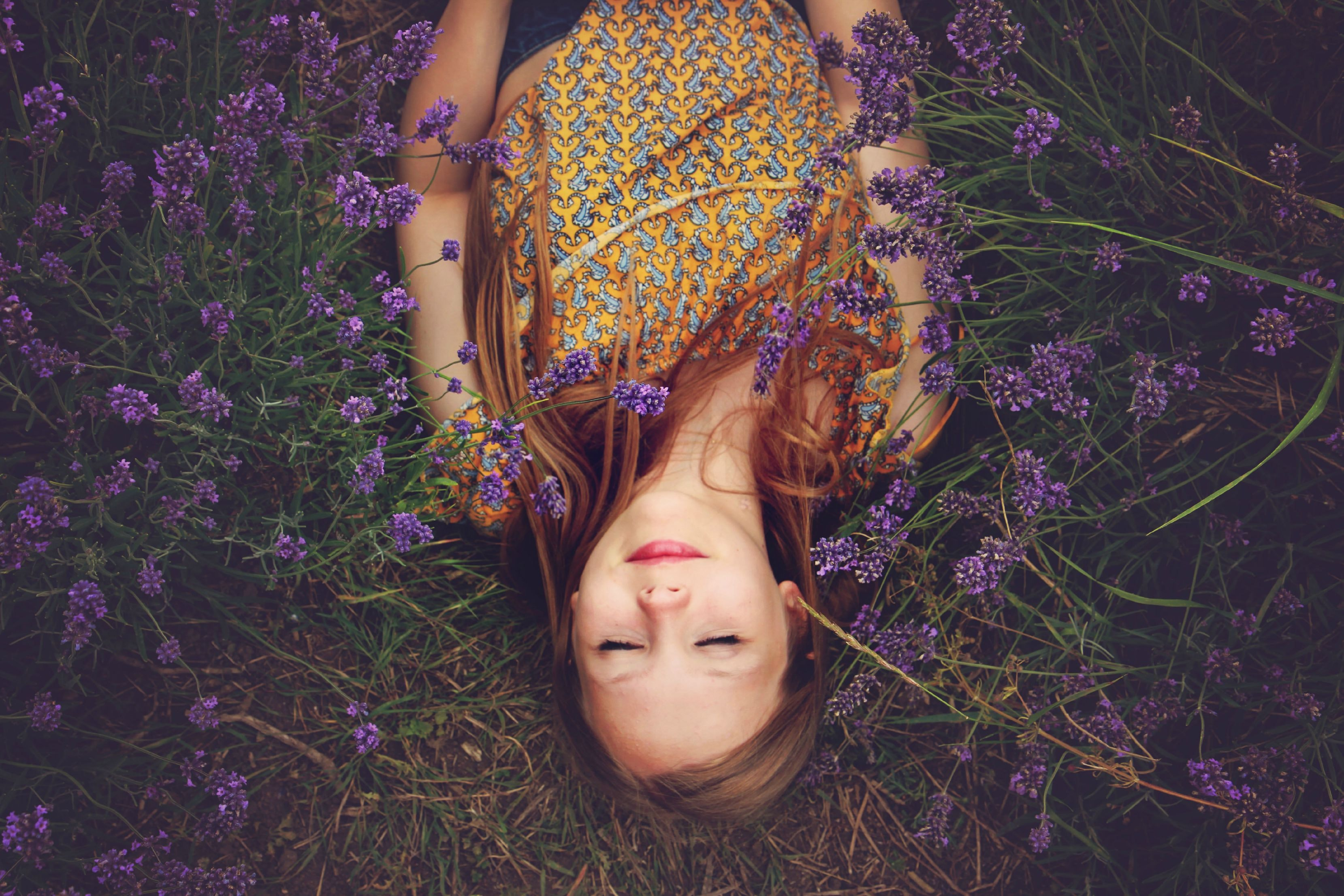 Photo of a light-skinned woman laying on the ground amidst lavender plants. Her face appears serene.