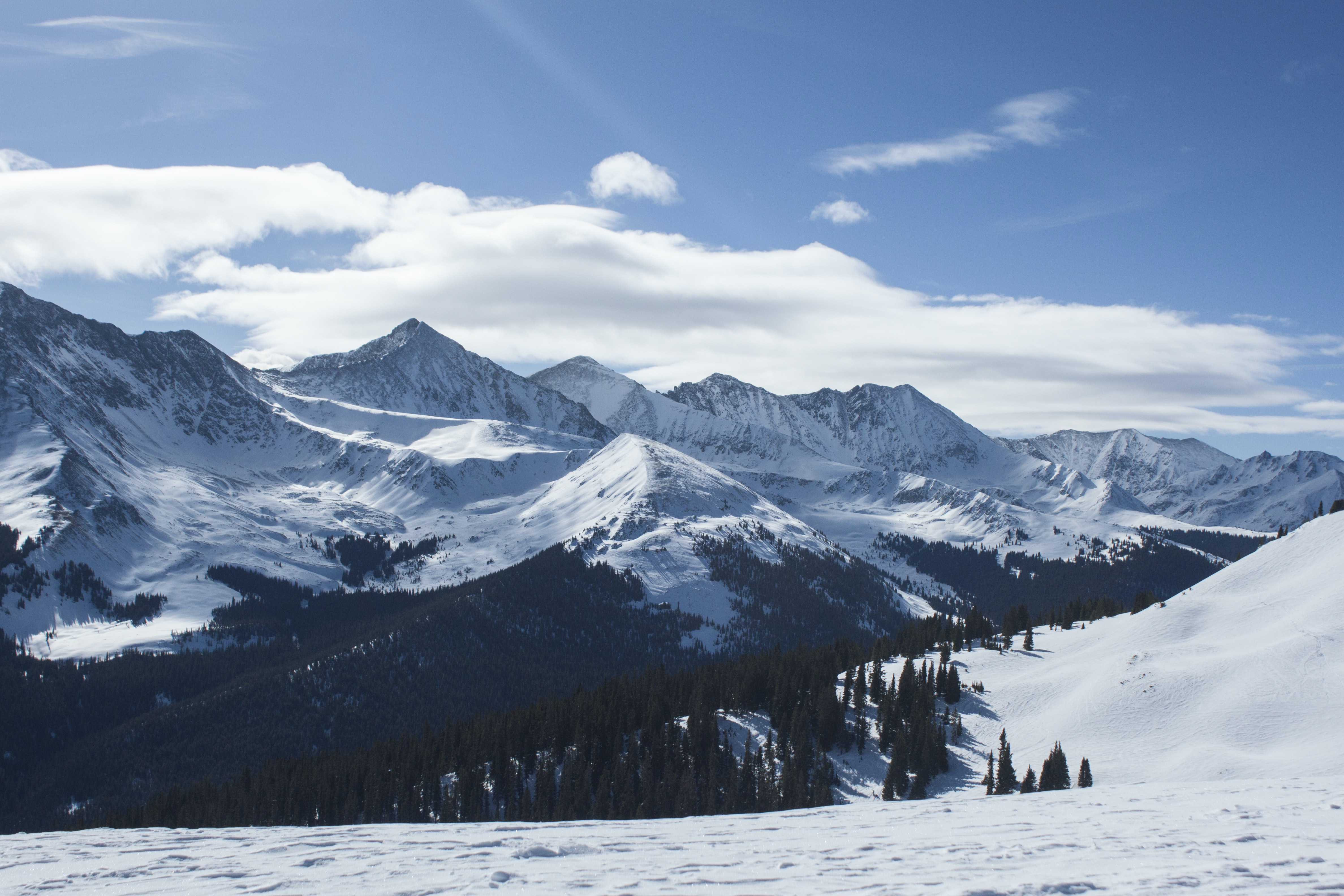 The snowy peaks of Copper Mountain range with a forest at its feet