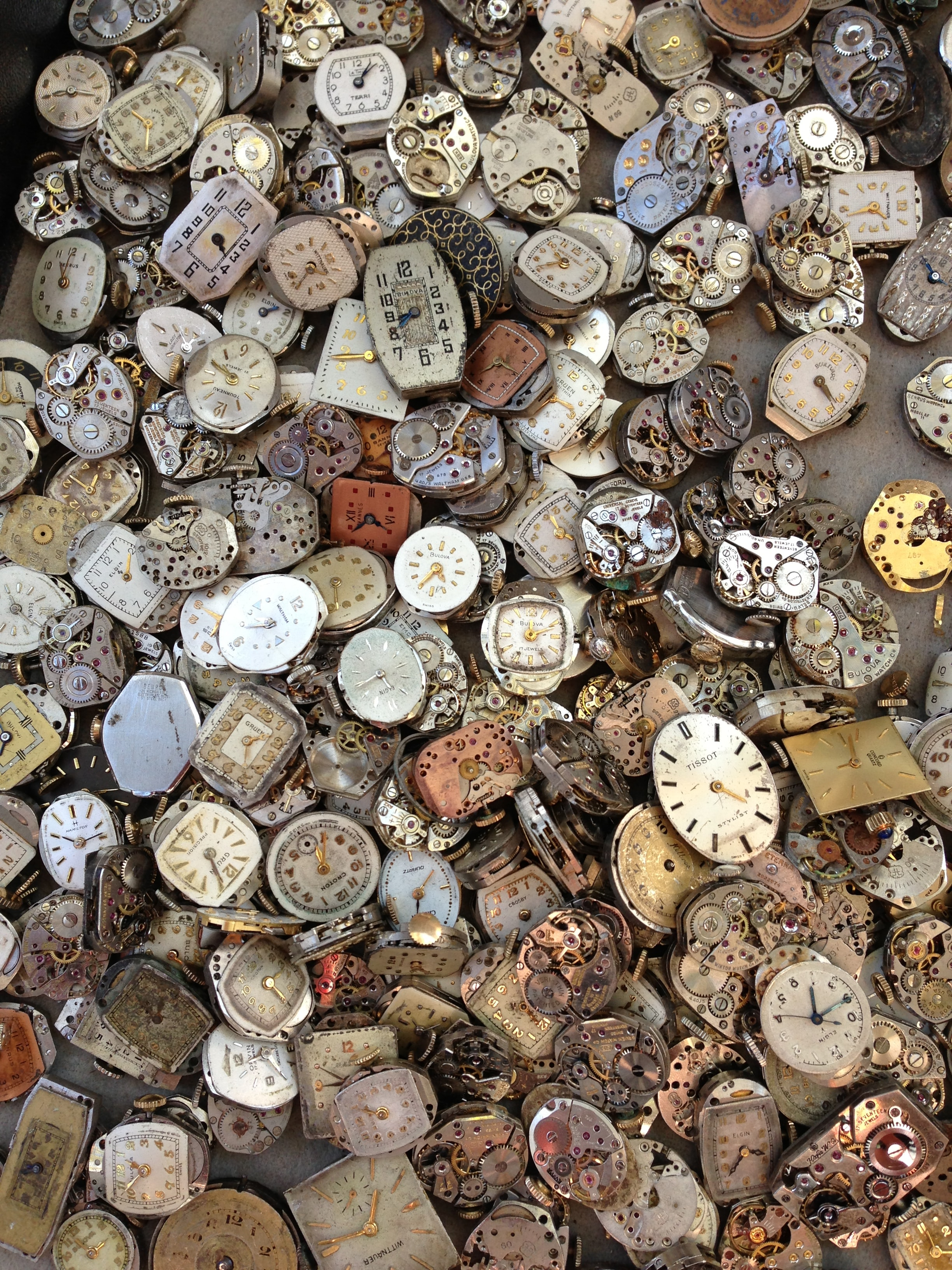 A large heap of broken antique watches and clocks