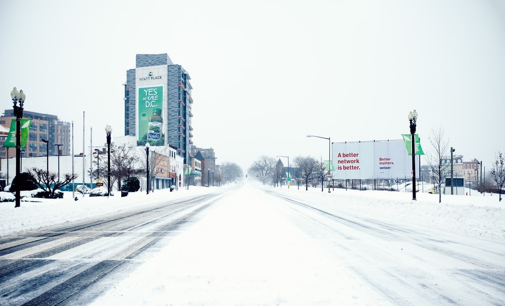 snow covered road near high rise buildings during daytime